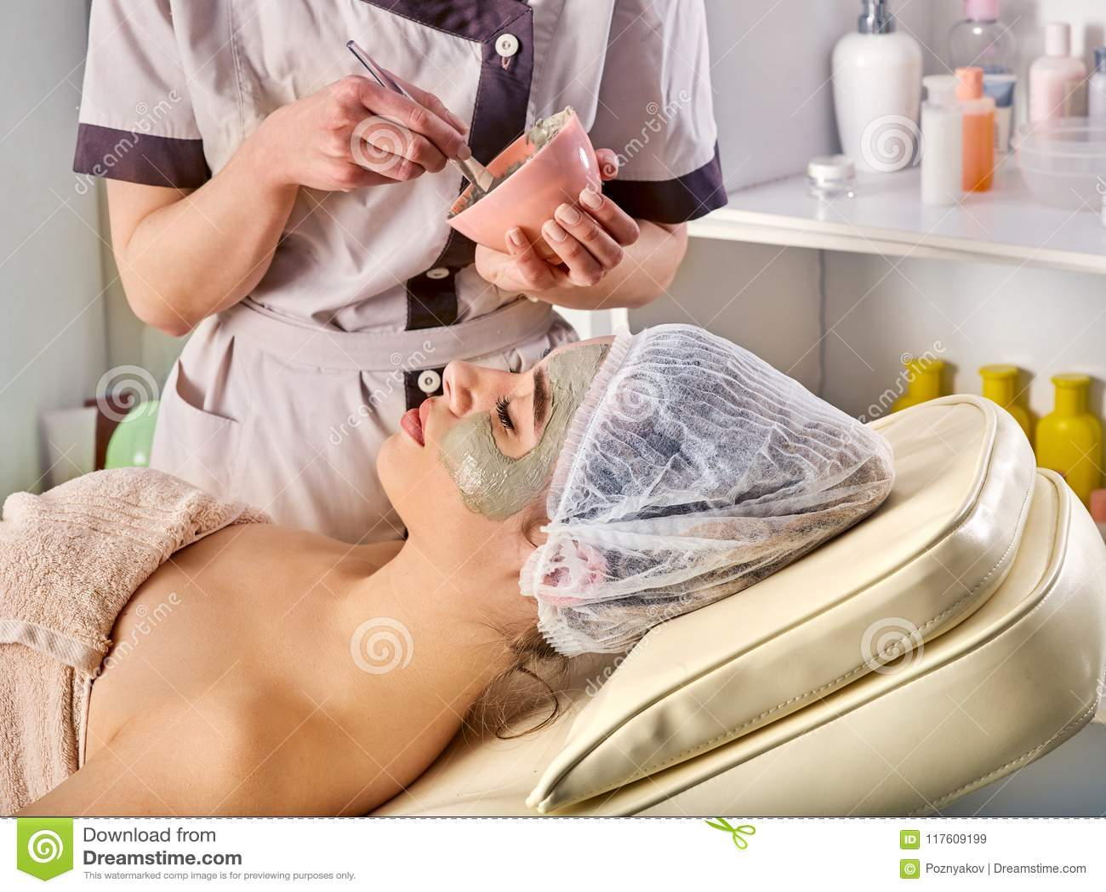 Masque facial de boue de femme dans le salon de station thermale Massage de visage