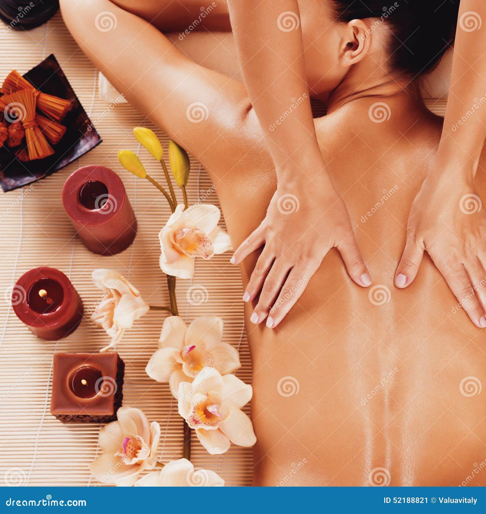 Massör som gör massage på kvinnabaksida i brunnsortsalong