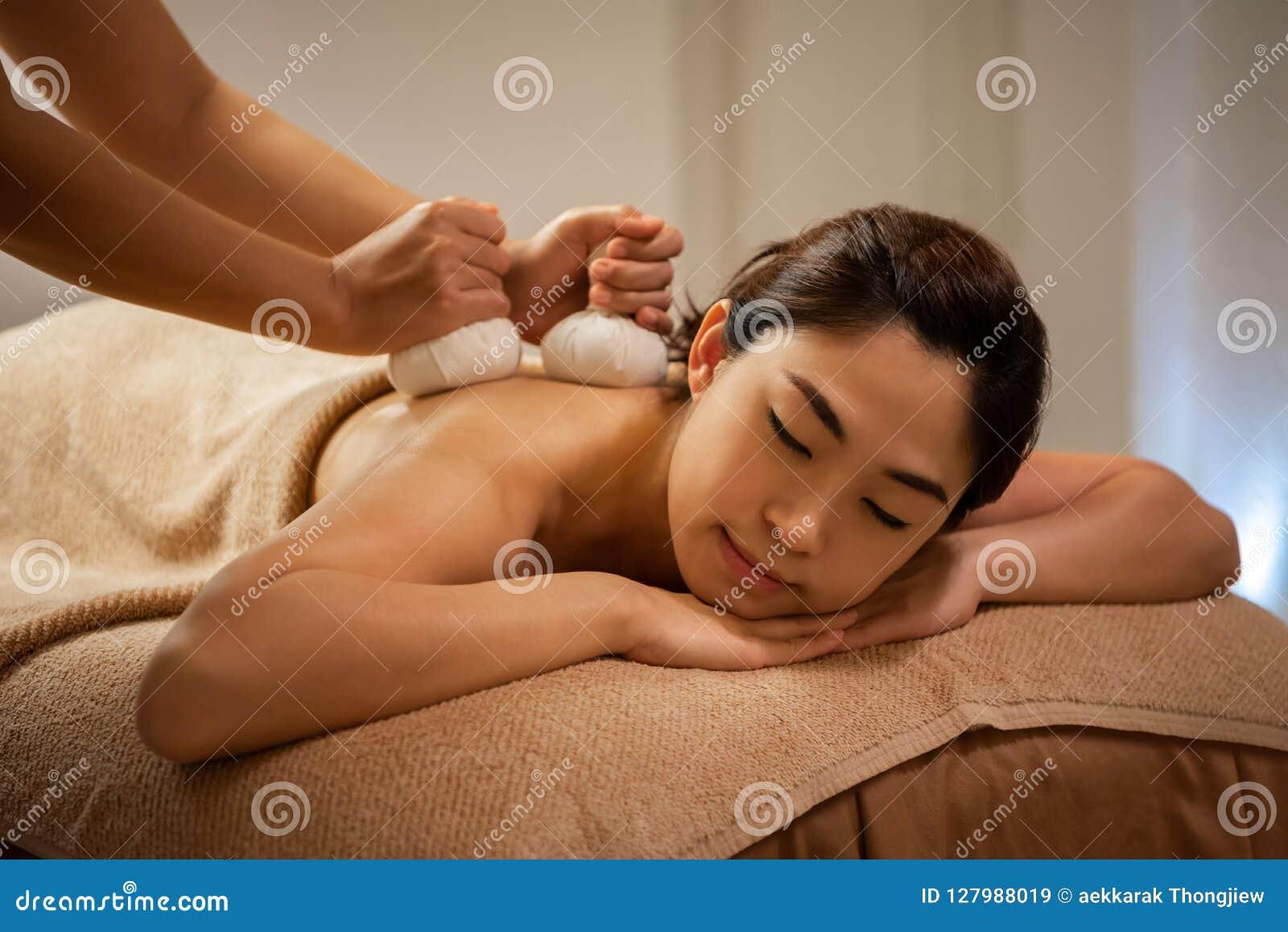 Massös som gör massage på asiatisk kvinnlig kropp i brunnsortsalongen