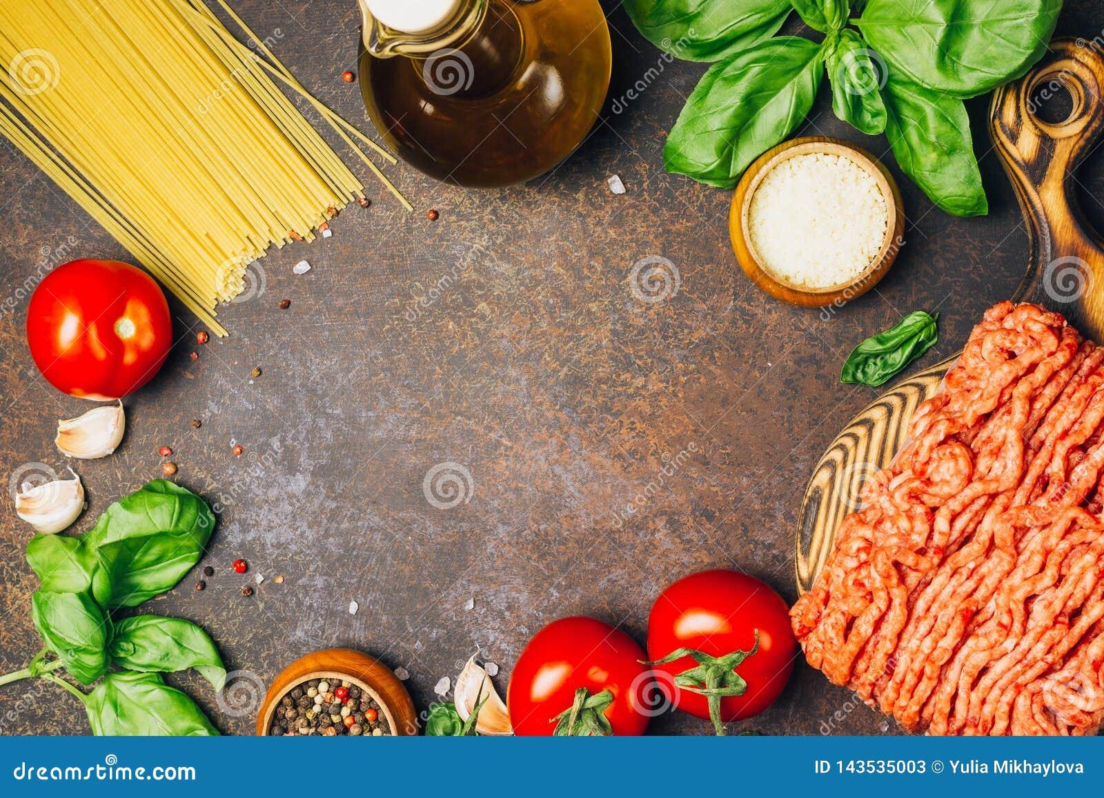 Massa bolonhesa que cozinha o conceito: carne triturada crua, tomates, massa, Parmesão, alho, manjericão, azeite