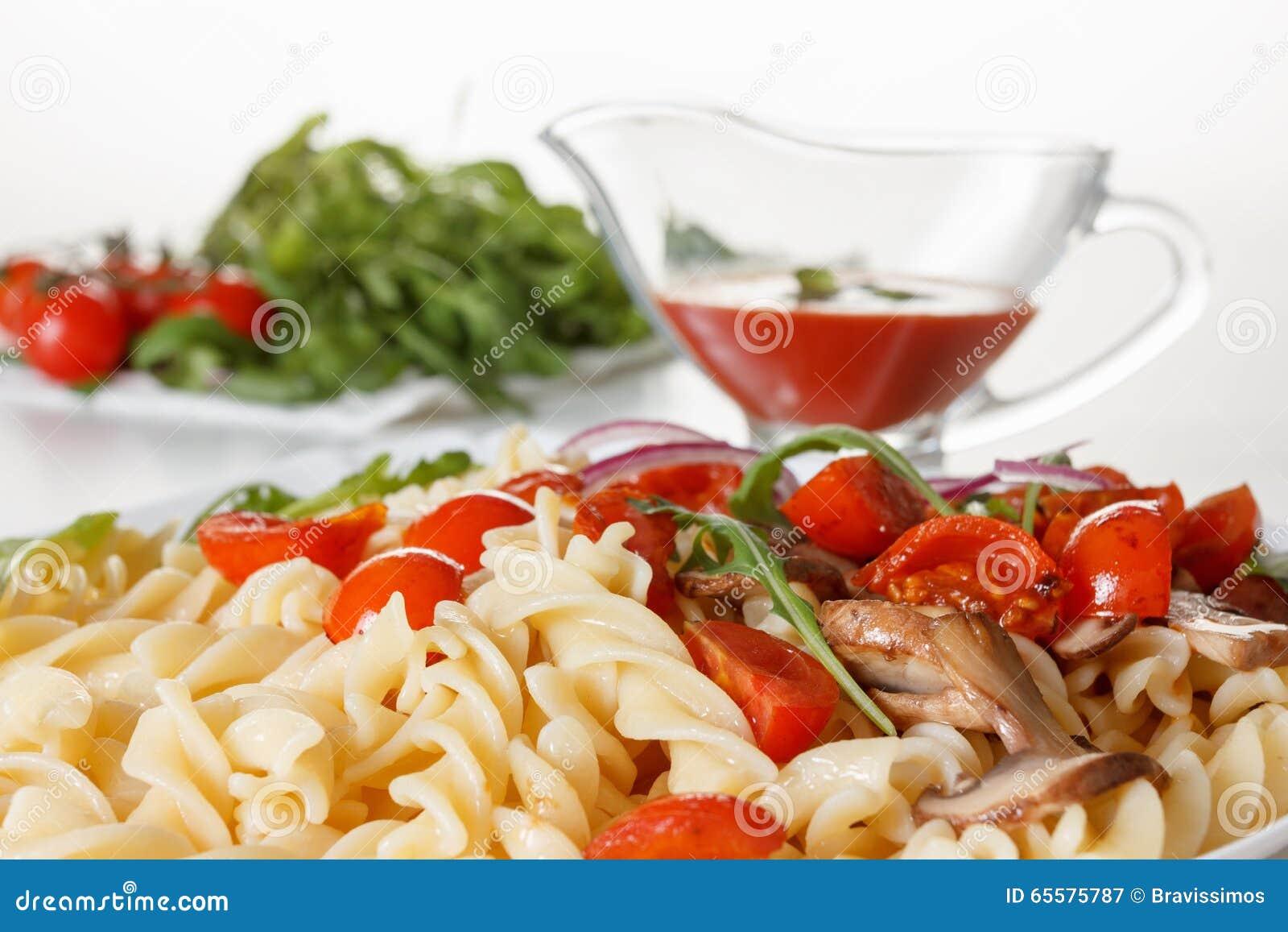 Massa com cogumelos, tomates de cereja e molho de tomate, alimento italiano closeup