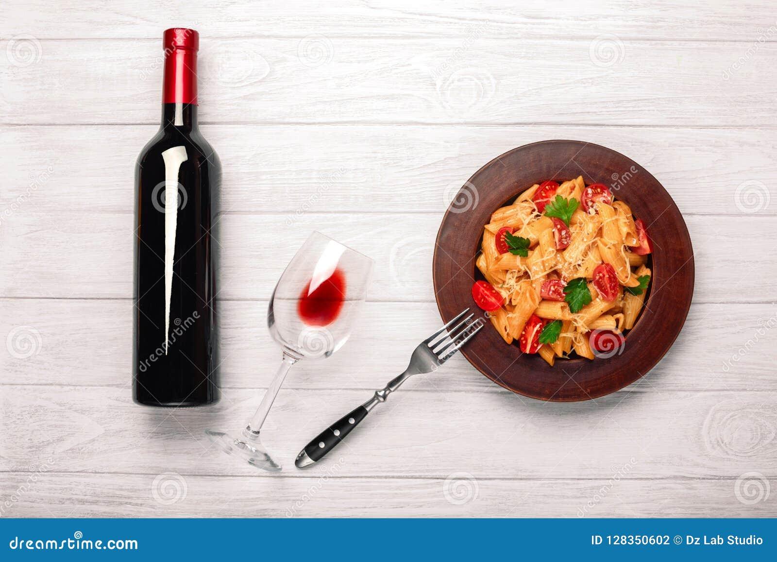 A massa com queijo, o tomate de cereja, o copo de vinho e a garrafa wine nas placas de madeira brancas