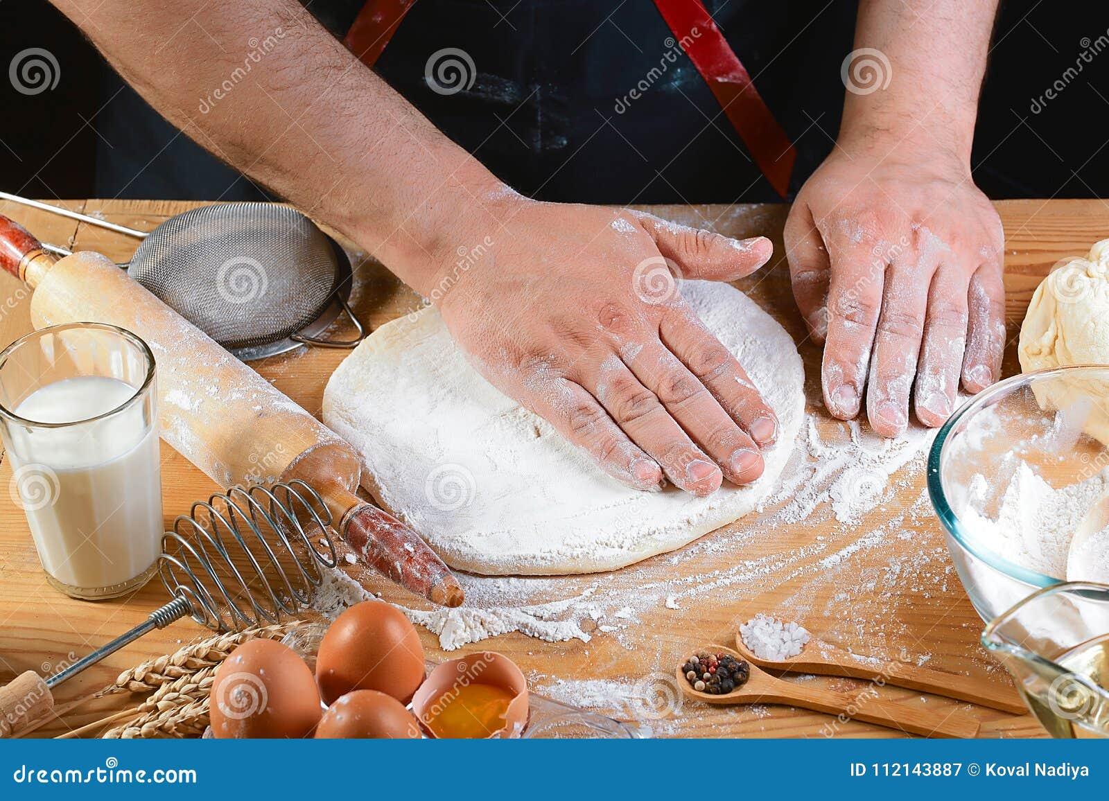 Massa do rolamento do padeiro com os ingredientes da receita do pão, da pizza ou da torta da farinha com mãos, alimento no fundo