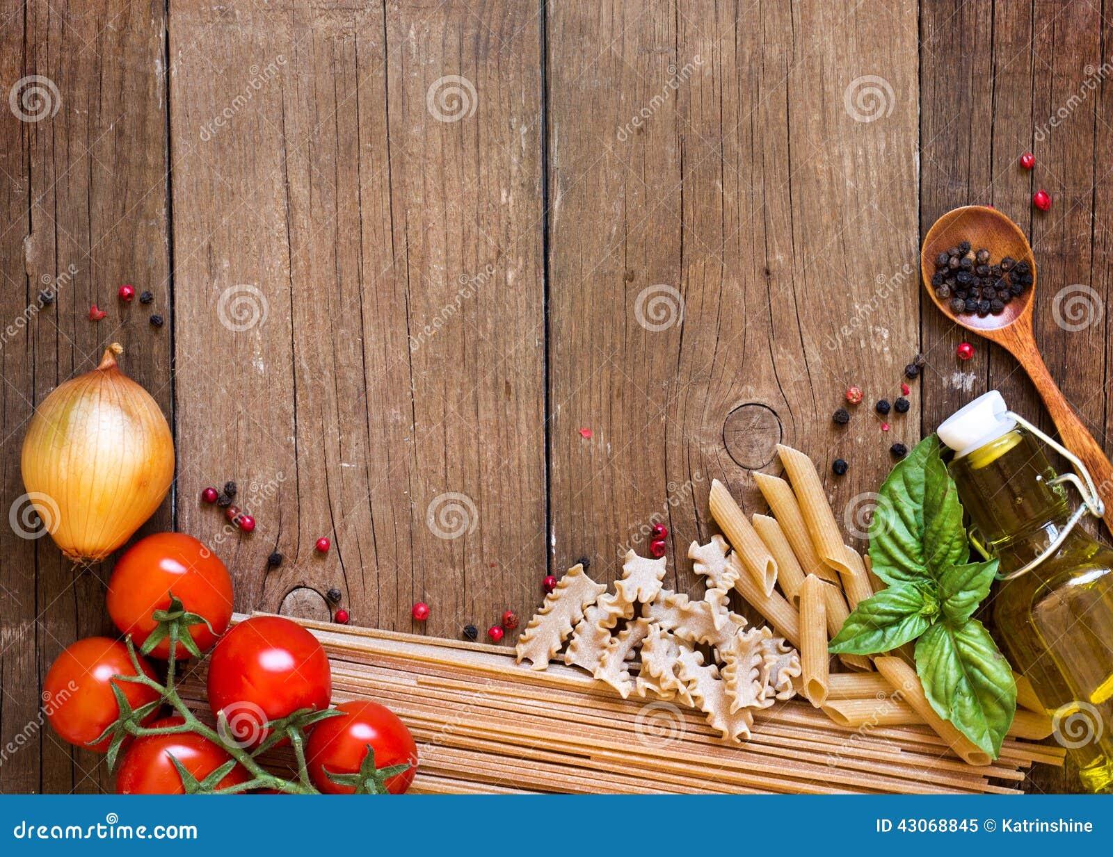 Massa, tomates, cebola, azeite e manjericão no fundo de madeira