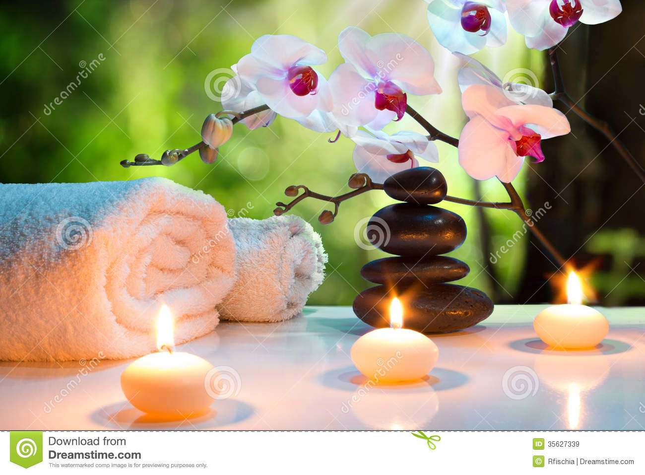 Massage composition spa with candles, orchids and black stones in garden