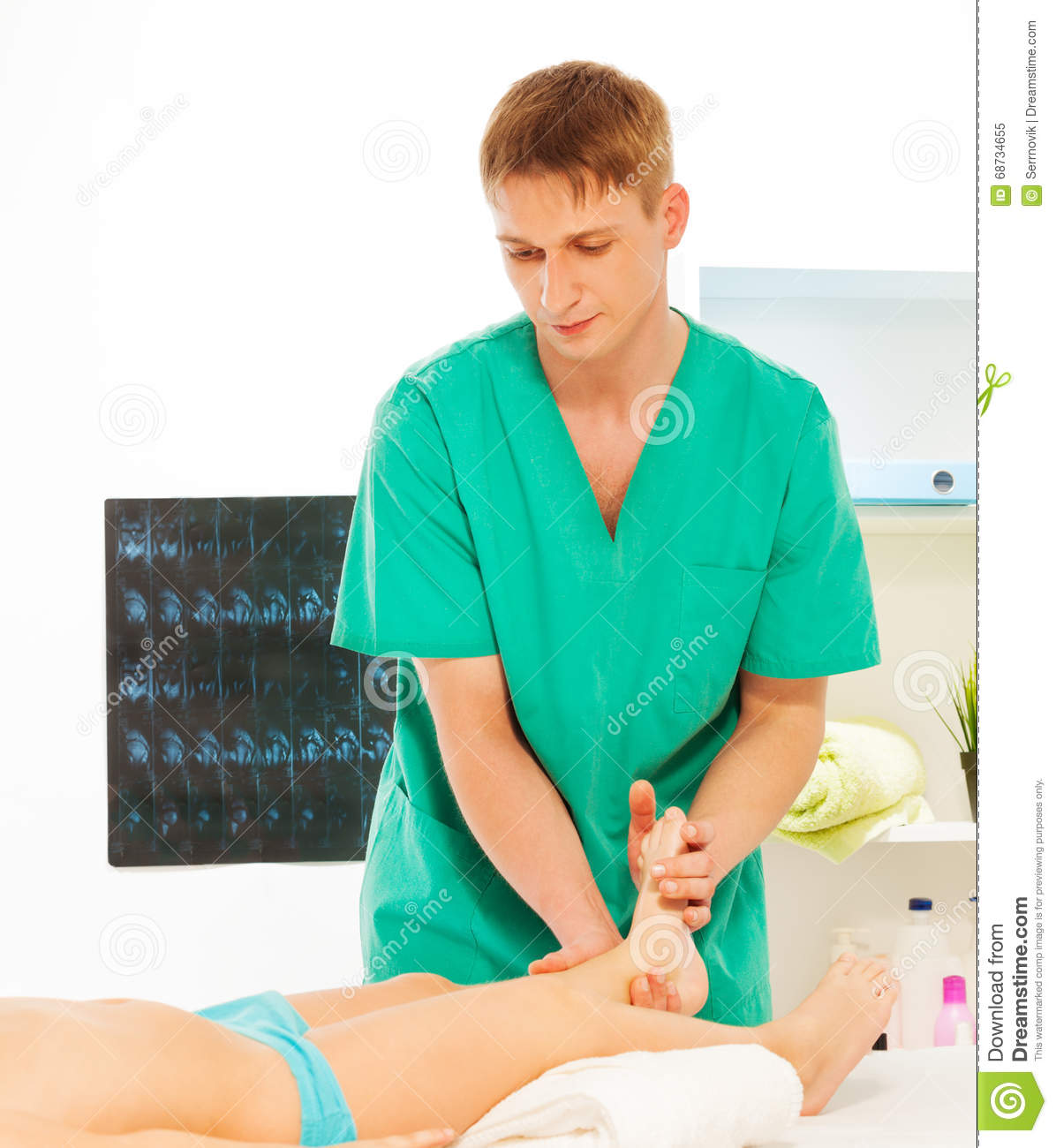 Massage Therapist Massaging Boy Foot At Cabinet Stock Image - Image: 68734655