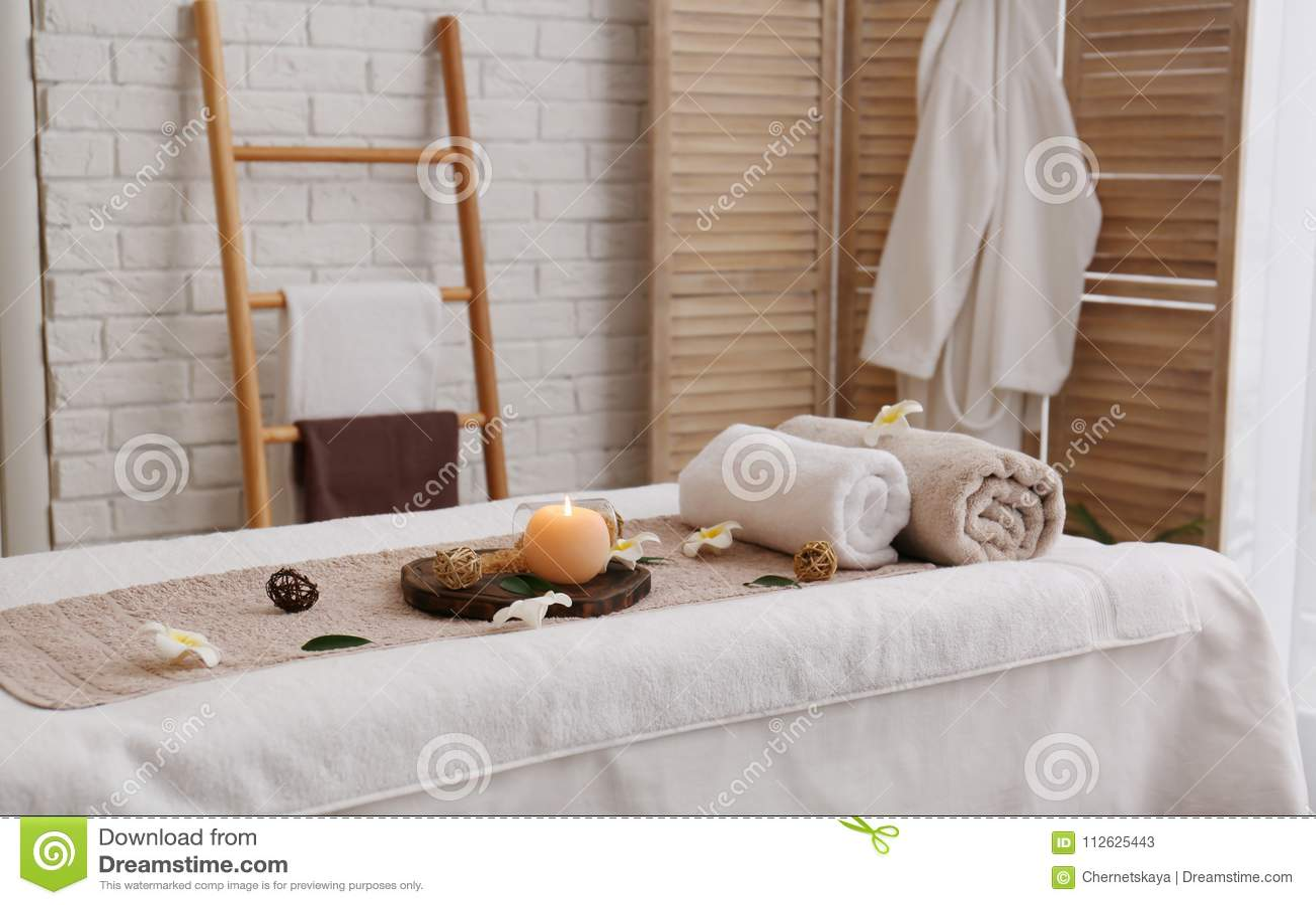 Massagetabell med handdukar, stearinljuset och havet som är salta i brunnsortsalong