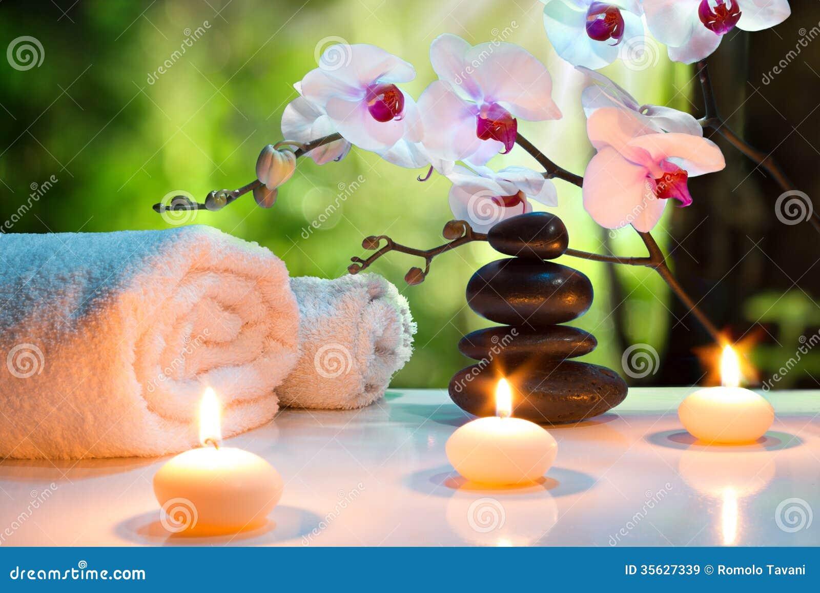 Massaggi la stazione termale della composizione con le candele, le orchidee e le pietre nere in giardino