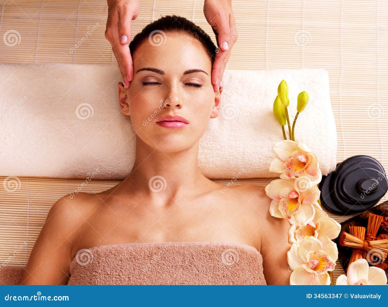 Massagista que faz a massagem a cabeça de uma mulher no salão de beleza dos termas