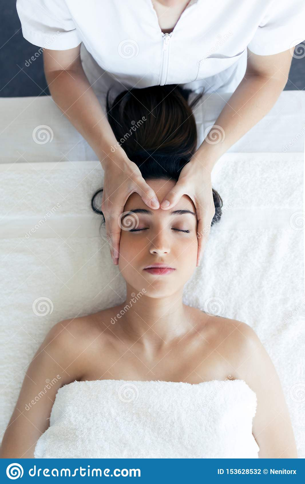 Masseur faisant le massage de visage thérapeutique à la jeune femme enceinte au centre de station thermale