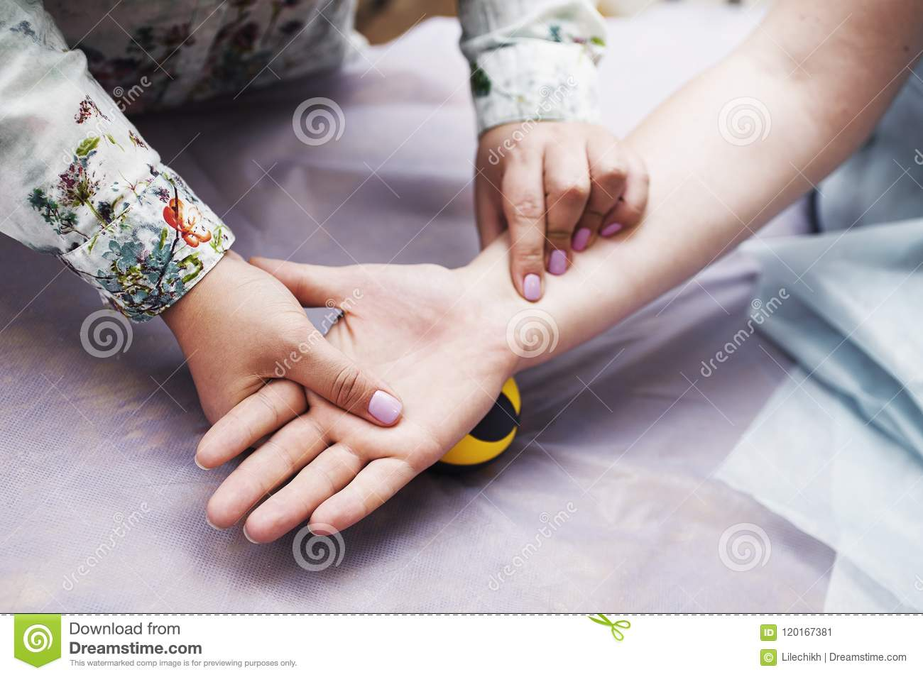 The masseur makes a hand massage to a woman in the medical office