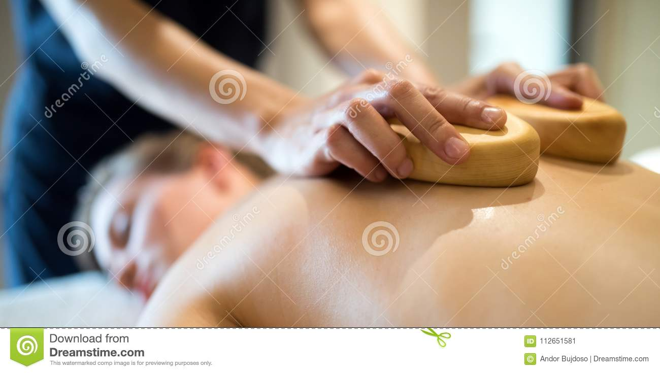 Masseur massaging masseuse at wellness resort