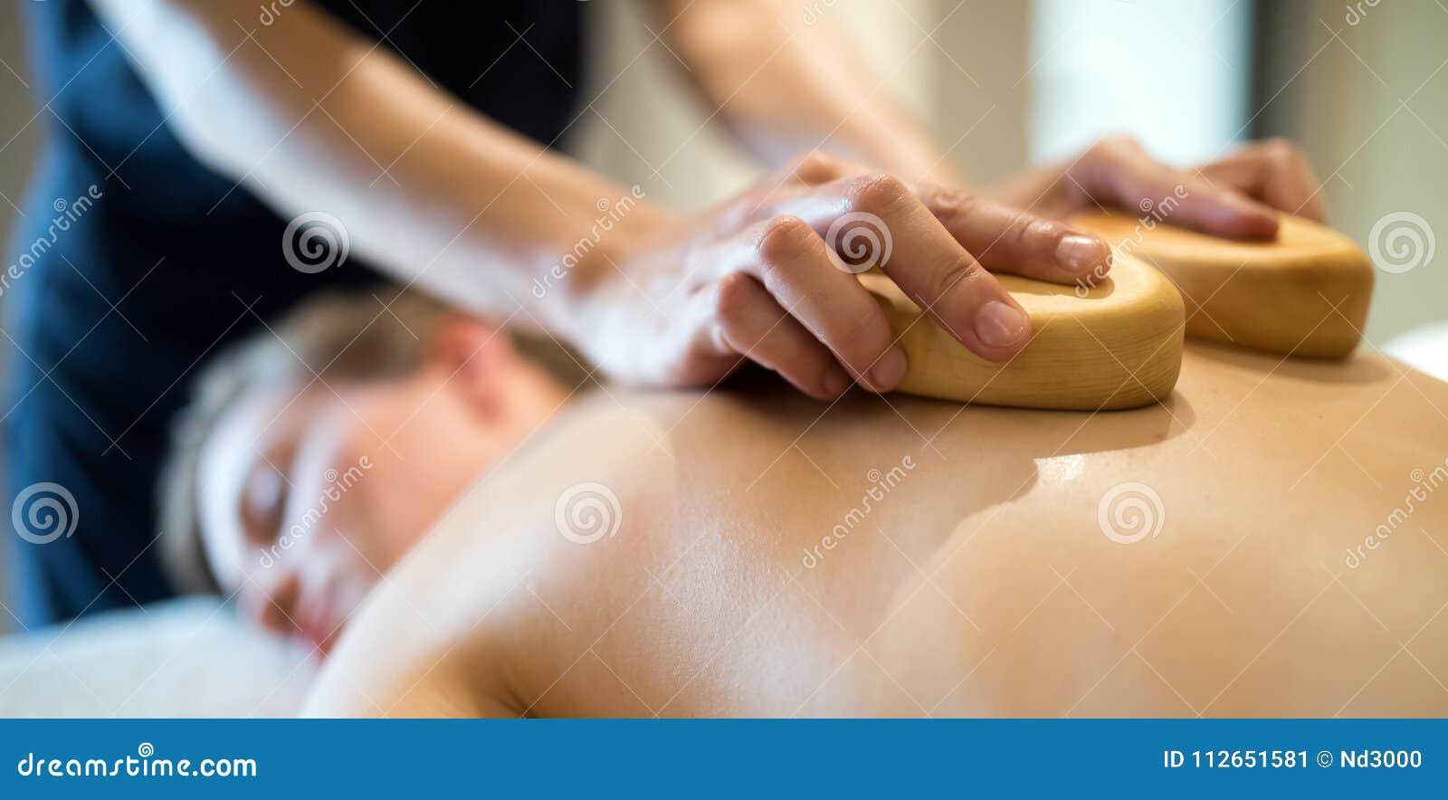 Masseur massant la masseuse à la station de vacances de bien-être
