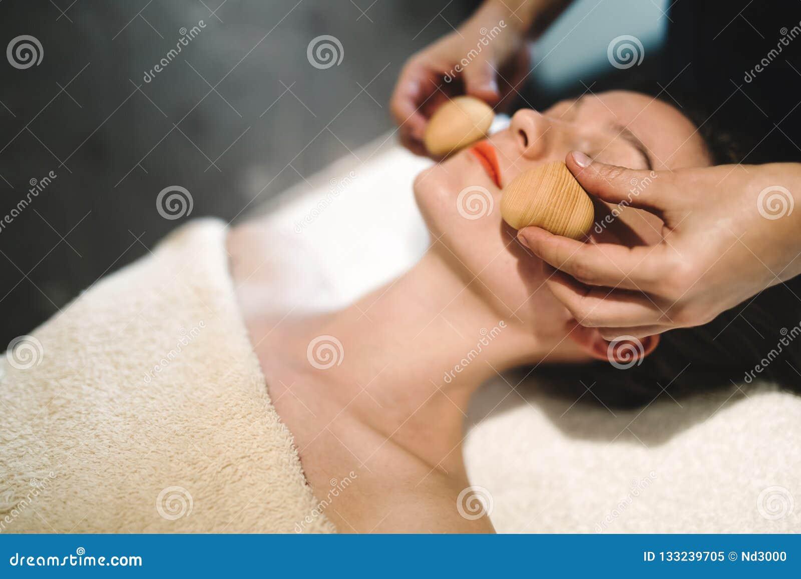 Masseur massant le visage avec les objets passionnés