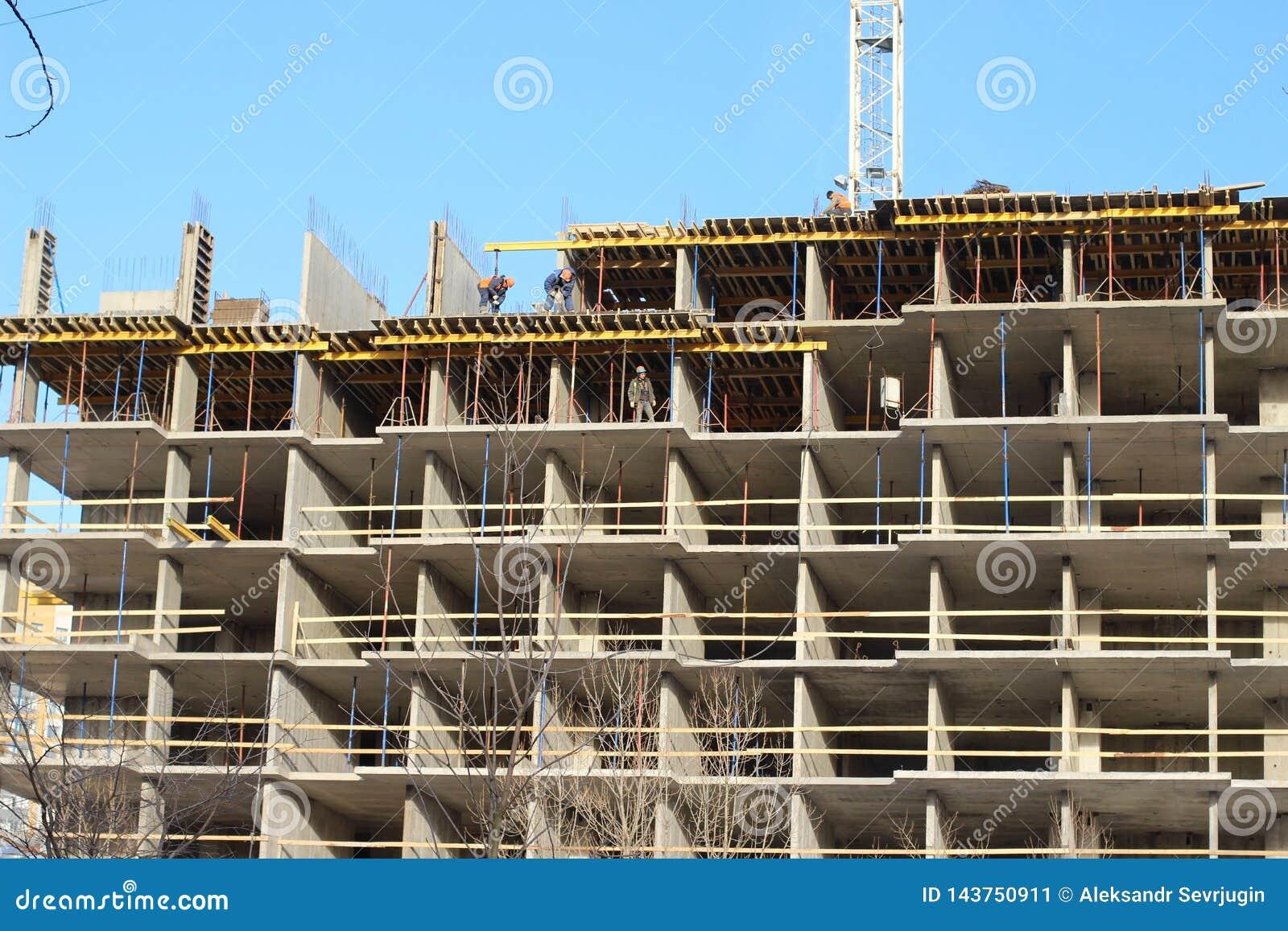 Massor av tornkonstruktionsplats med kranar och byggnad med bakgrund för blå himmel