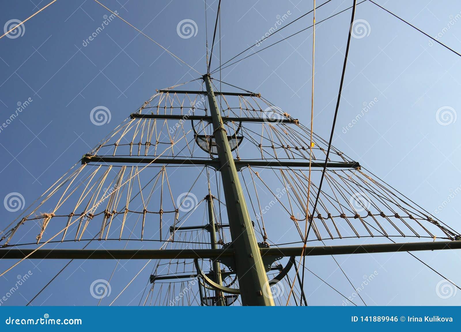 Mast op een jacht met heel wat kabels tegen een zonnige blauwe hemel op een de zomerdag