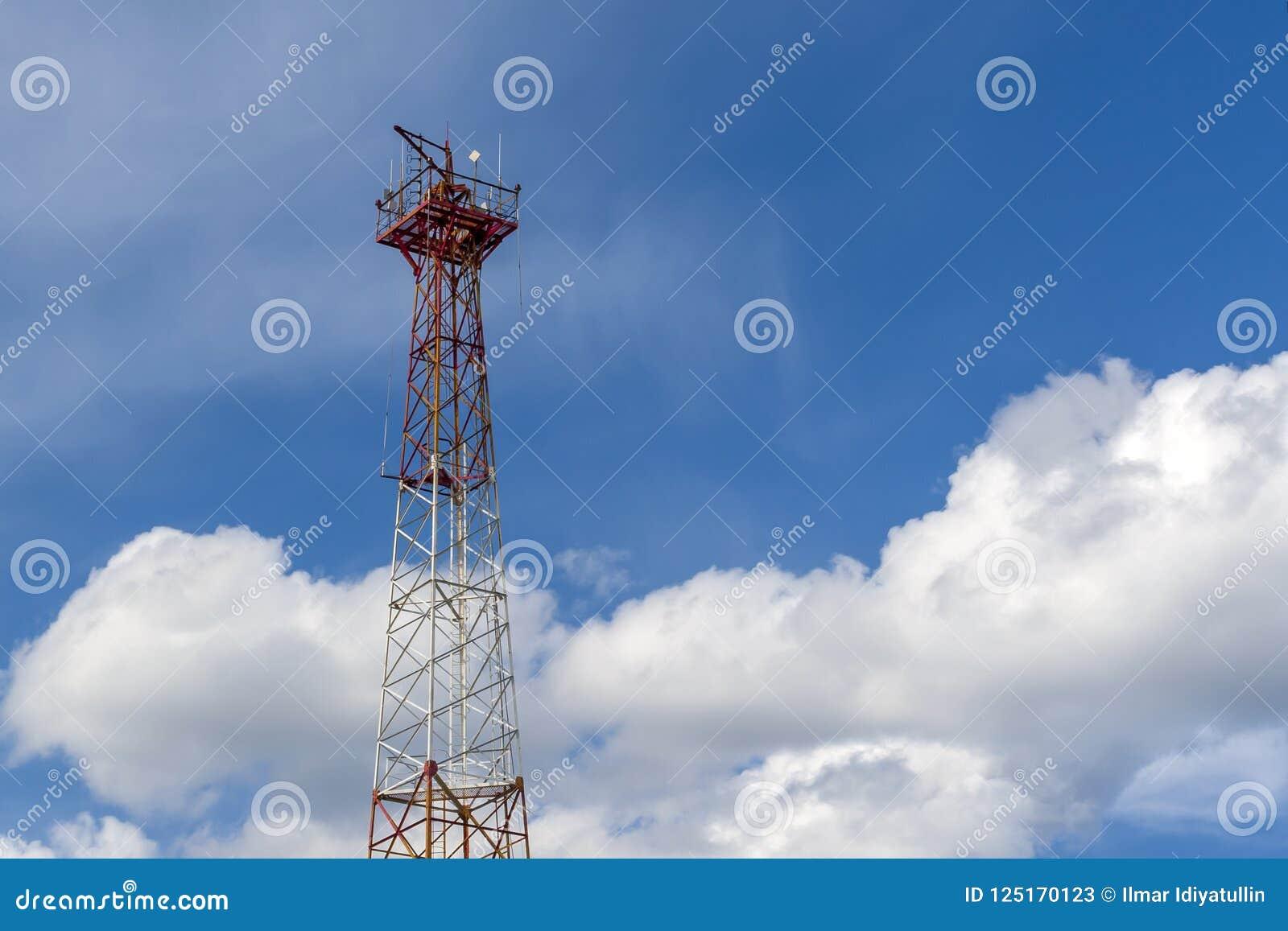 Mast van cellulaire mededeling over een achtergrond van witte wolken