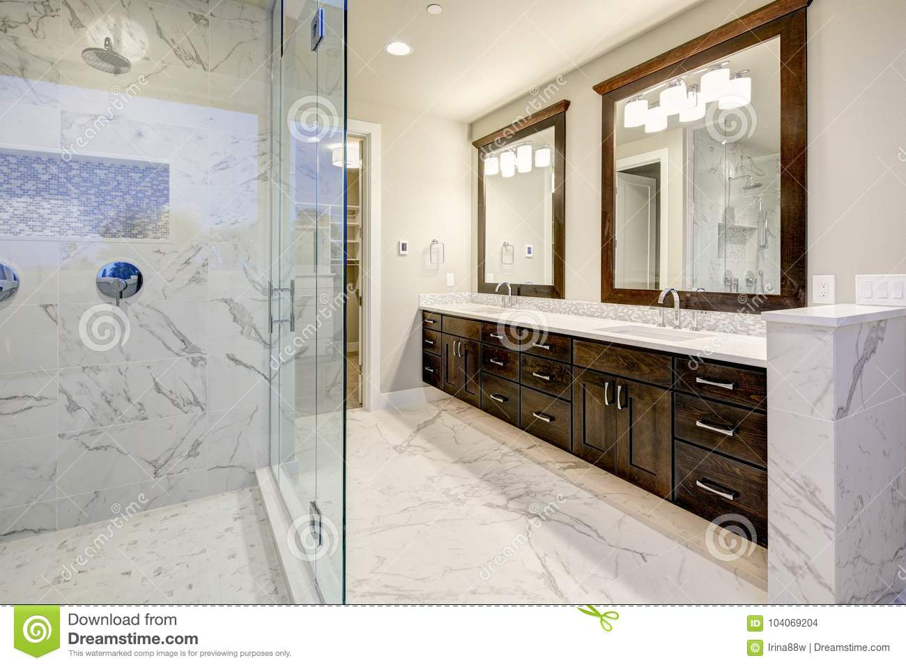 Bright and airy master bathroom features white modern double vanity with rich brown cabinets and marble walk in shower northwest usa