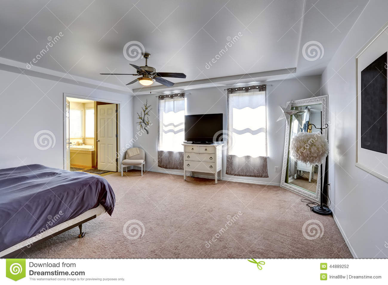 Master bedroom with tv and large mirror in the corner stock photo
