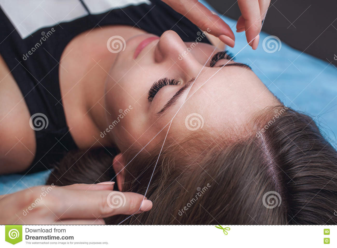 Master corrects makeup, gives shape and thread plucks eyebrows in a beauty salon.