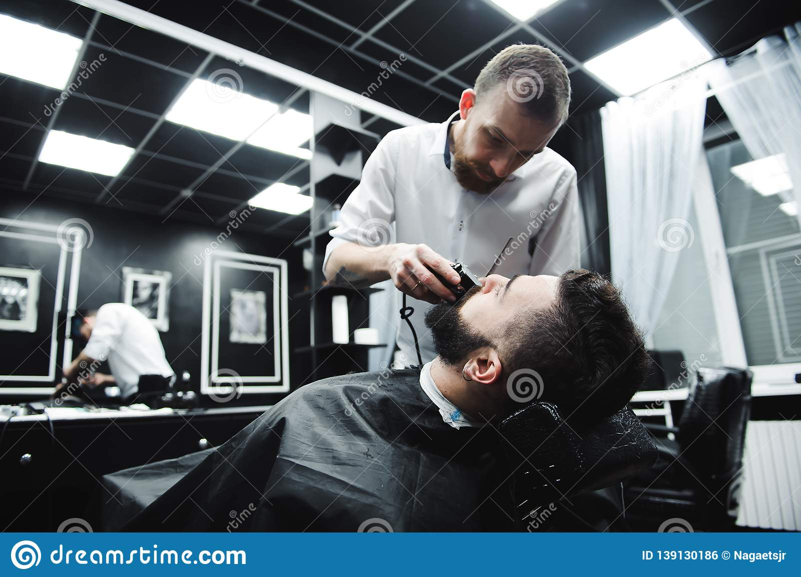 Master cuts hair and beard of men in the barbershop, hairdresser