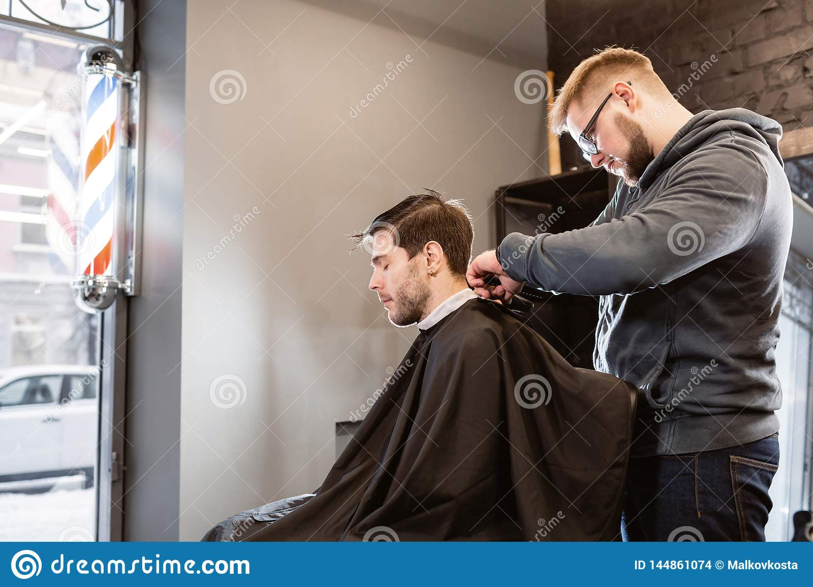 Master cuts hair and beard of men in the barbershop, hairdresser makes hairstyle for a young man. Barber work with