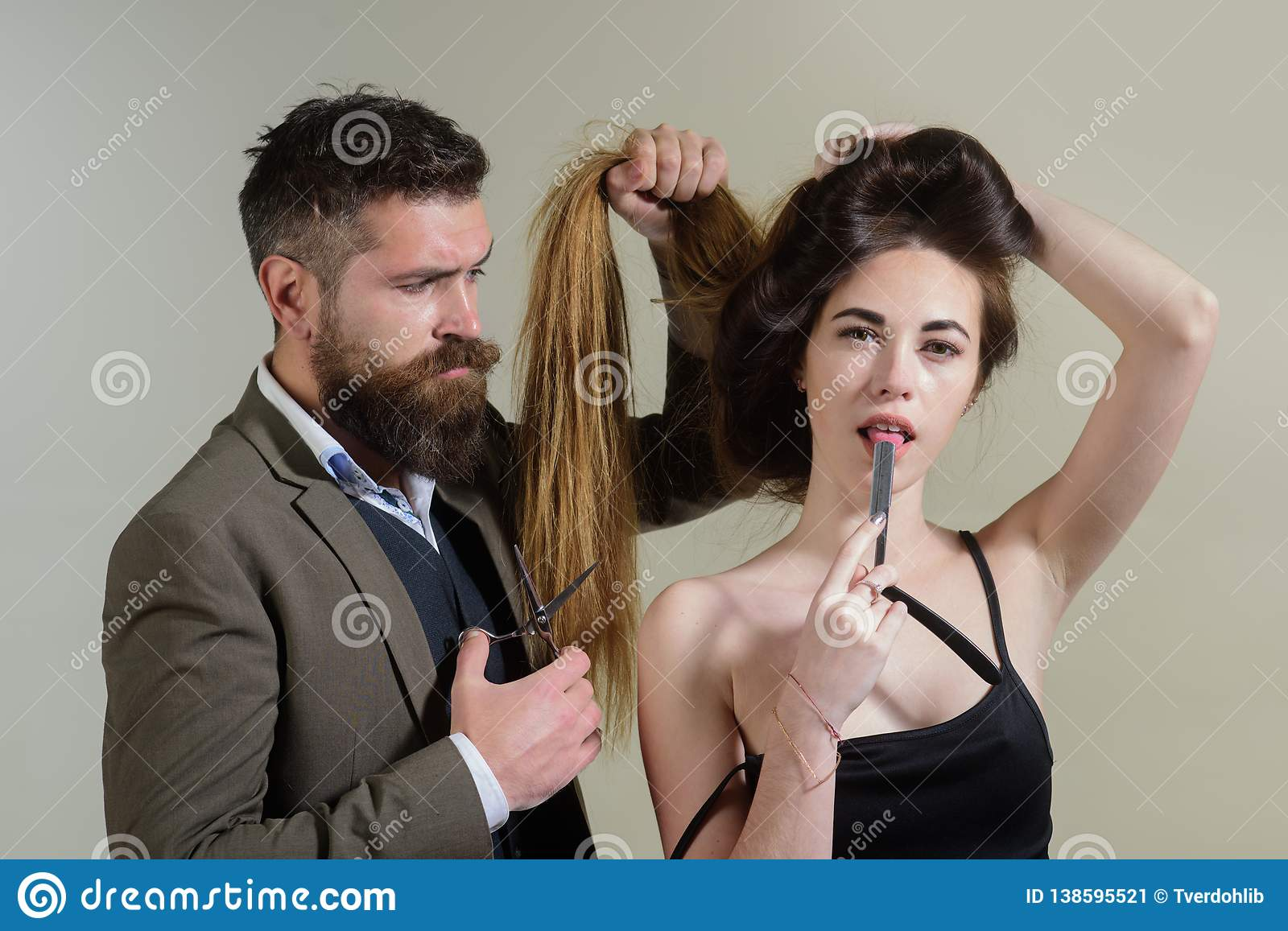 Master hairdresser does hairstyle and style with scissors and comb. Hairdressers work for a woman at the hair salon