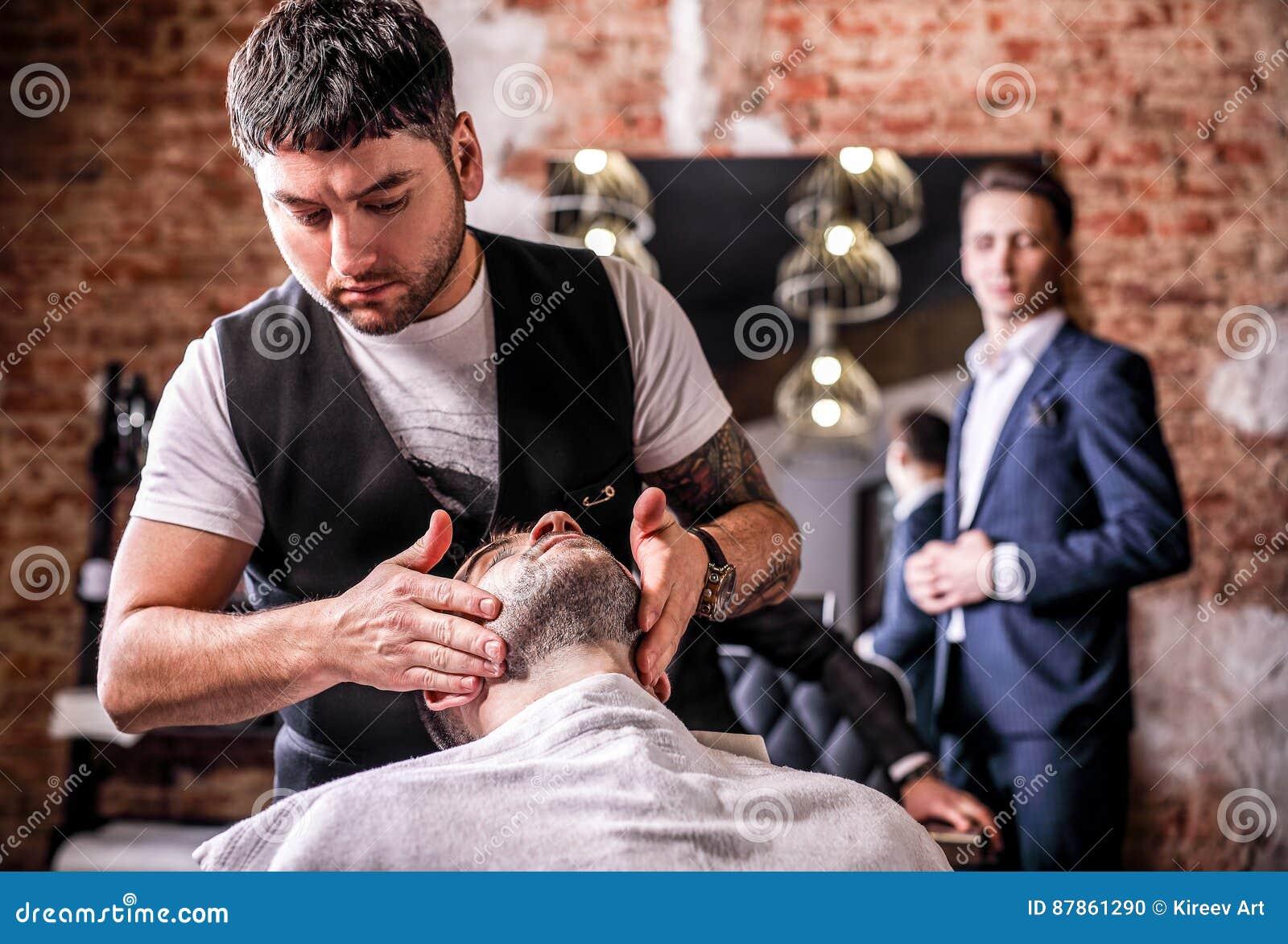 Master makes beards correction in barbershop salon. Close up photo.