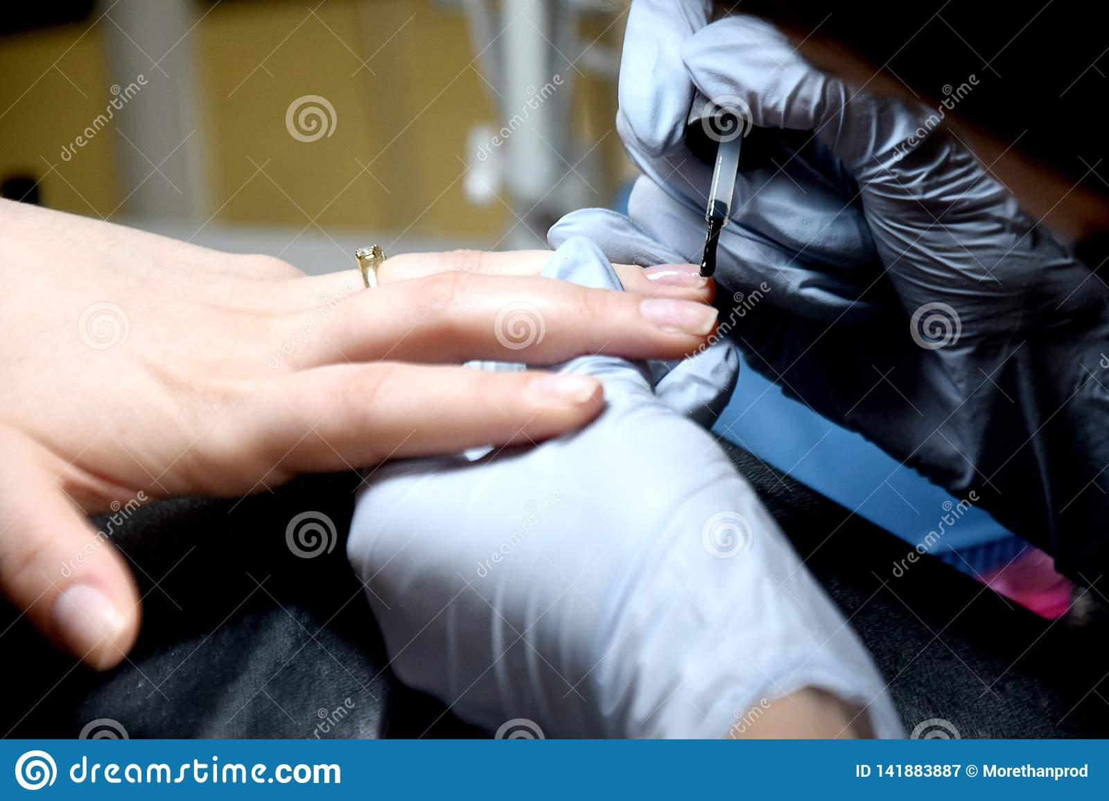 The master makes a manicure. Relaxing day at beauty salon. Manicurist master makes manicure on woman`s hand. Girl paint nails