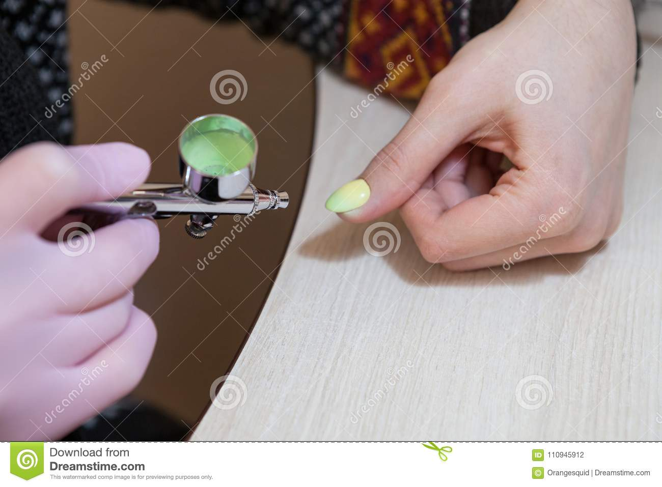 The Master Does The Design On The Nails With An Airbrush Stock