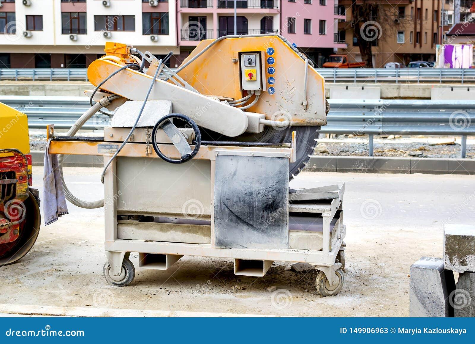 Maszyna dla ciąć brukowe cegiełki przy budowa drogi miejscem na miasto ulicie asfaltowej budynku maszyny maszynerii nowo?ytna dro