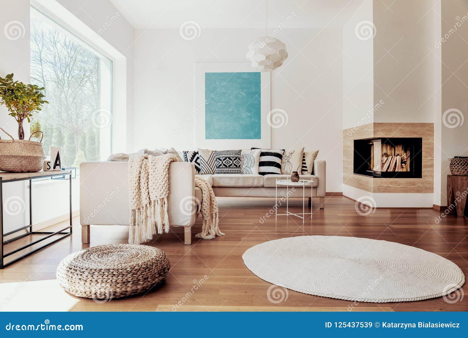 Matérias têxteis bege e brancas e uma luz esférica moderna do pendente em um interior ensolarado, tranquilo da sala de visitas co