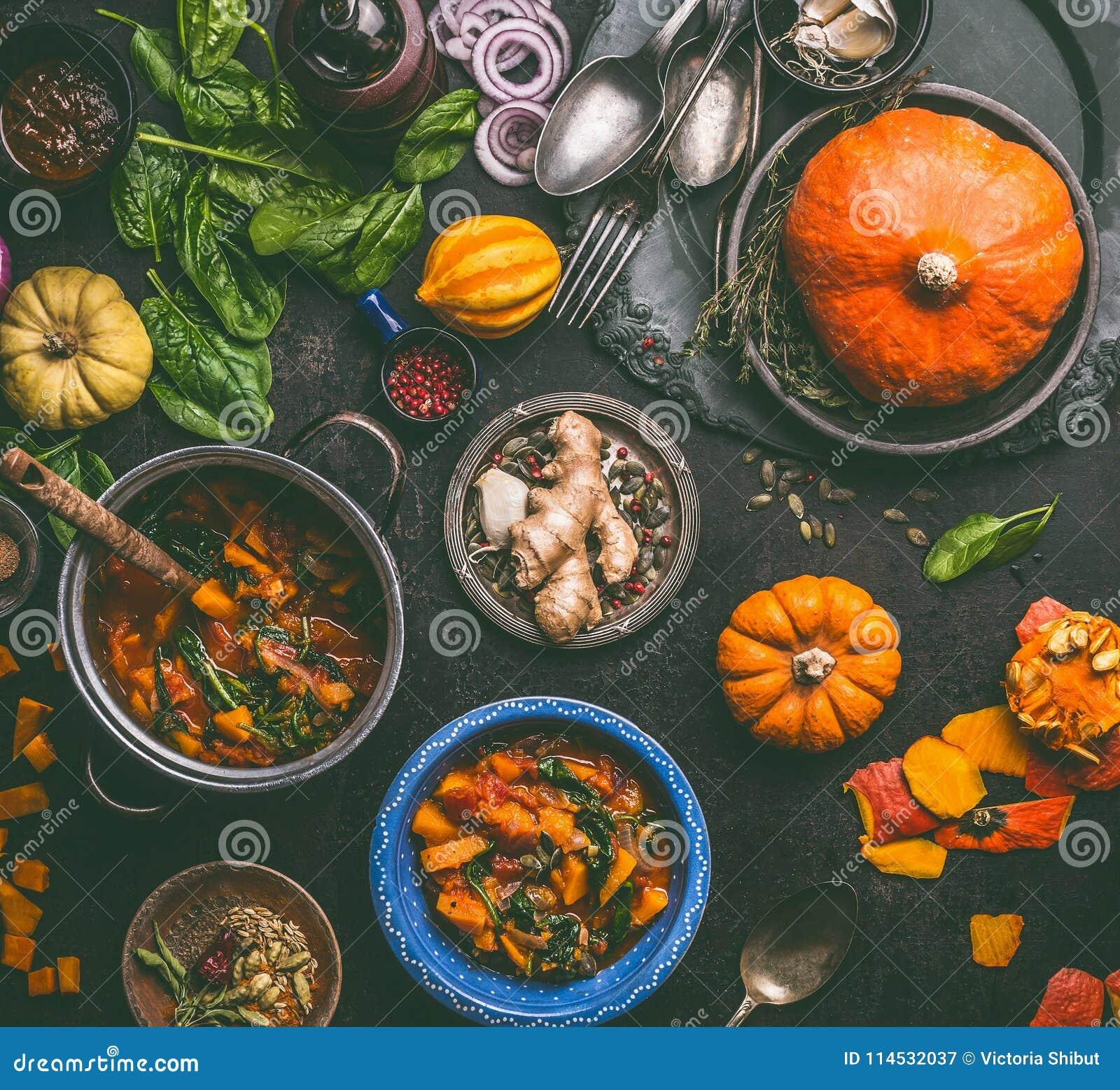 Mat och matlagning för höst säsongsbetonad med pumpa Mörkt lantligt köksbord med hjälpmedel, bunkar, skedar, hel och klippt pumpa