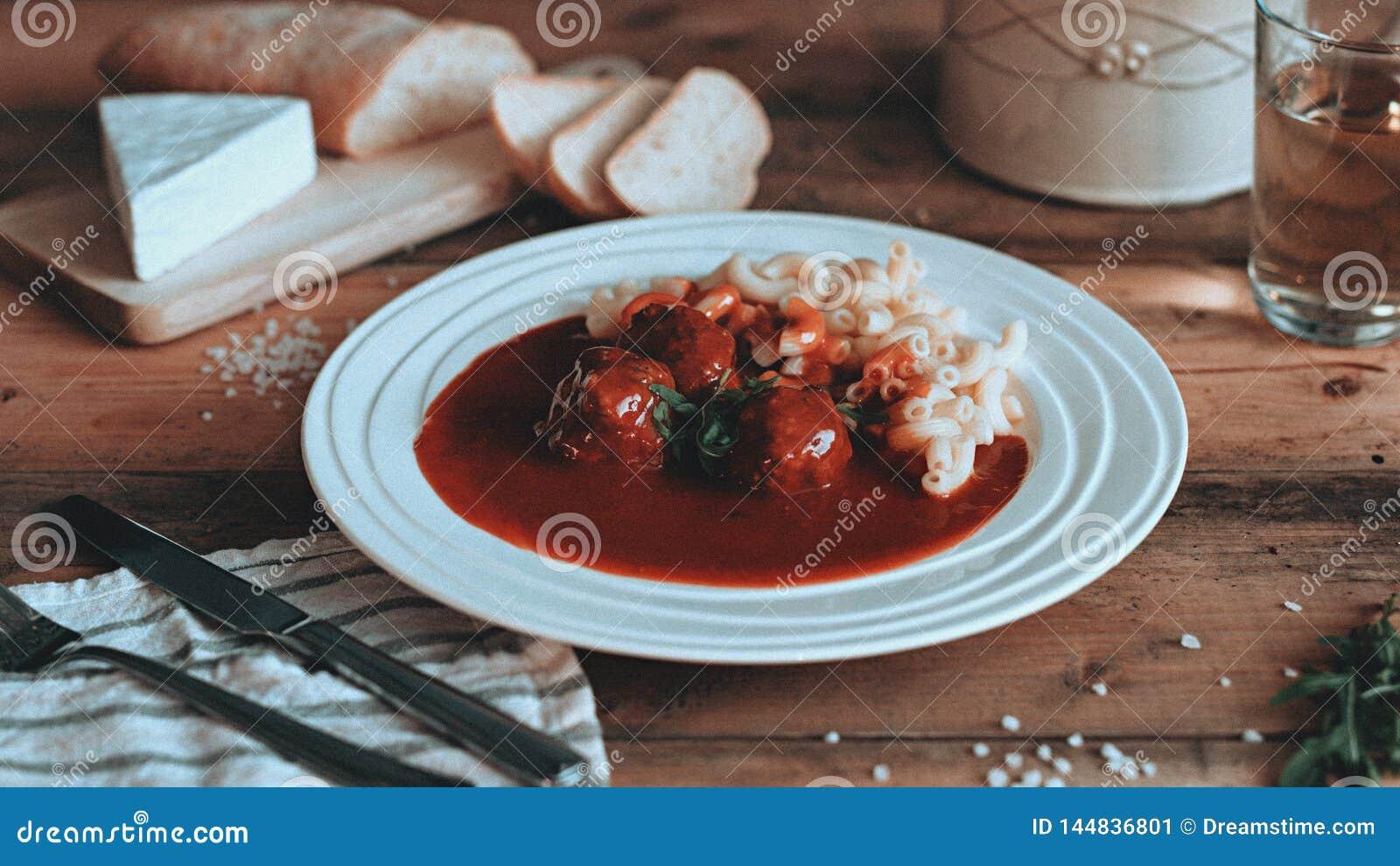 Mat som utformar tomatsås med pasta på träplankorna