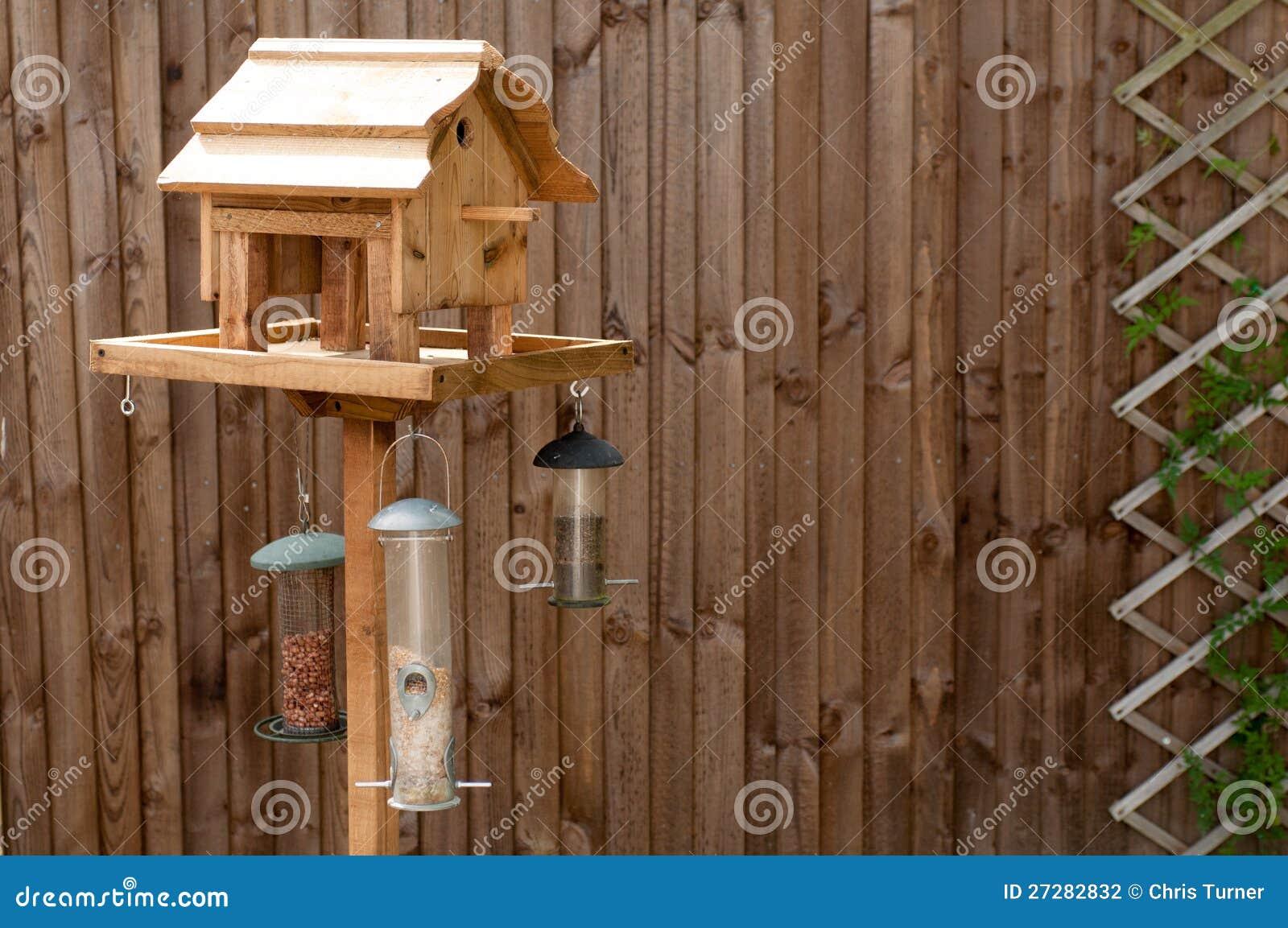 Matande tabell för fågel mot ett trästaket