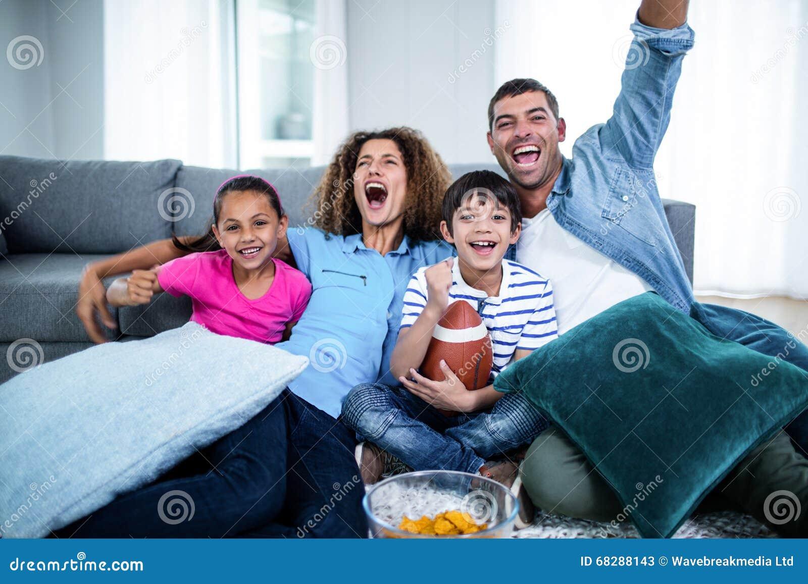 Match de observation de football américain de famille à la télévision