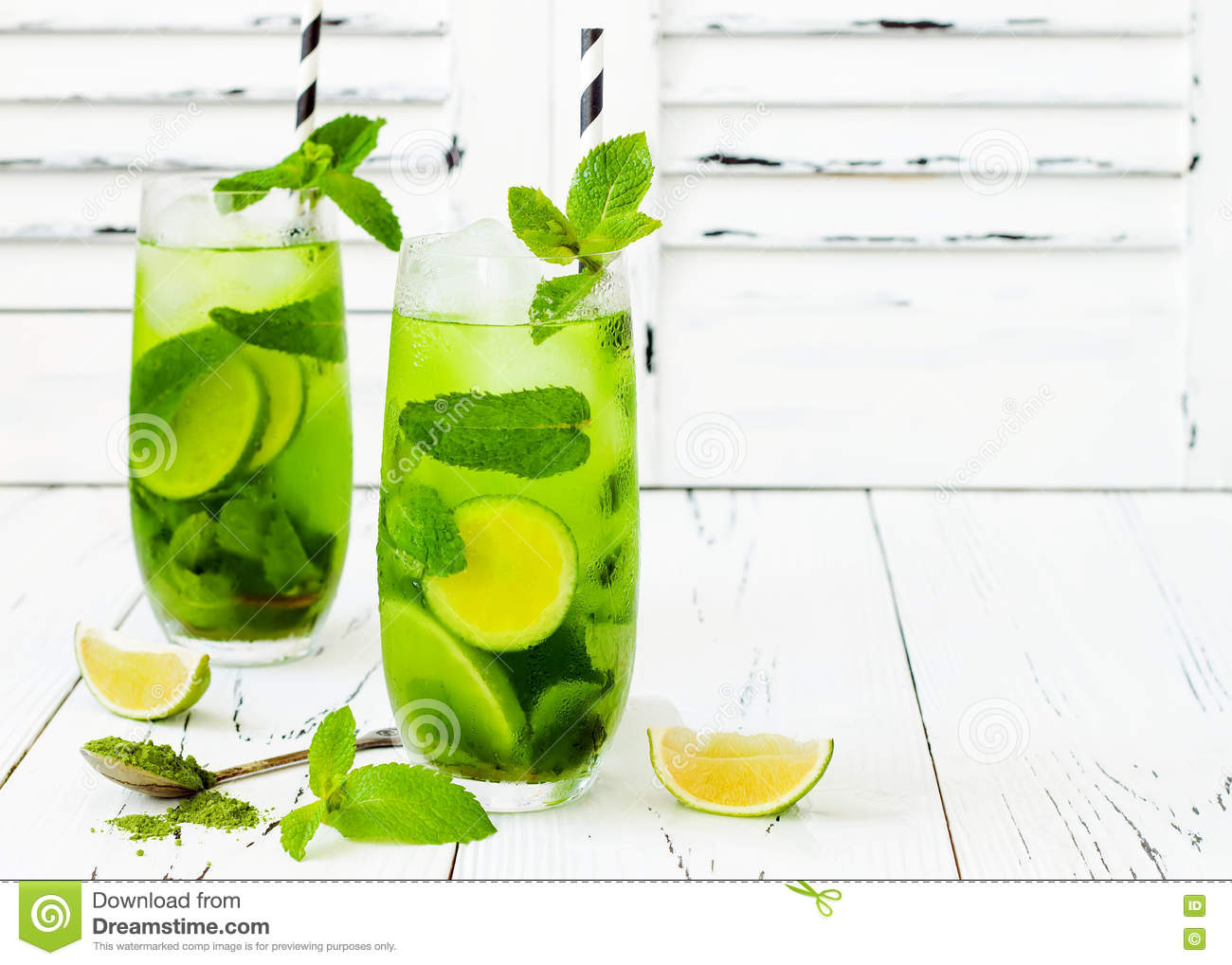 Matcha iced green tea with lime and fresh mint on white rustic background. Super food drink.