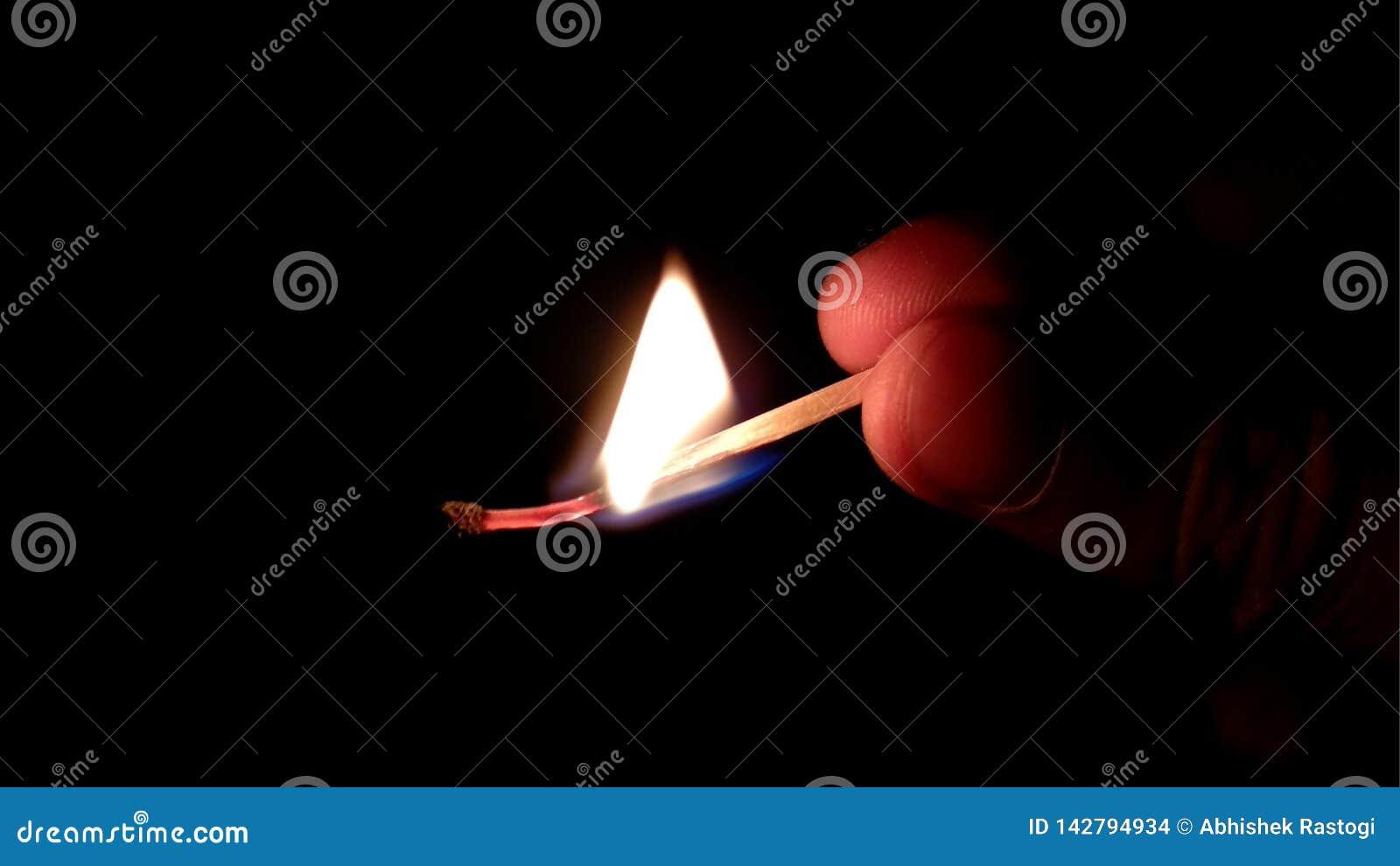 Matchstock, der gegen schwarzen Hintergrund brennt