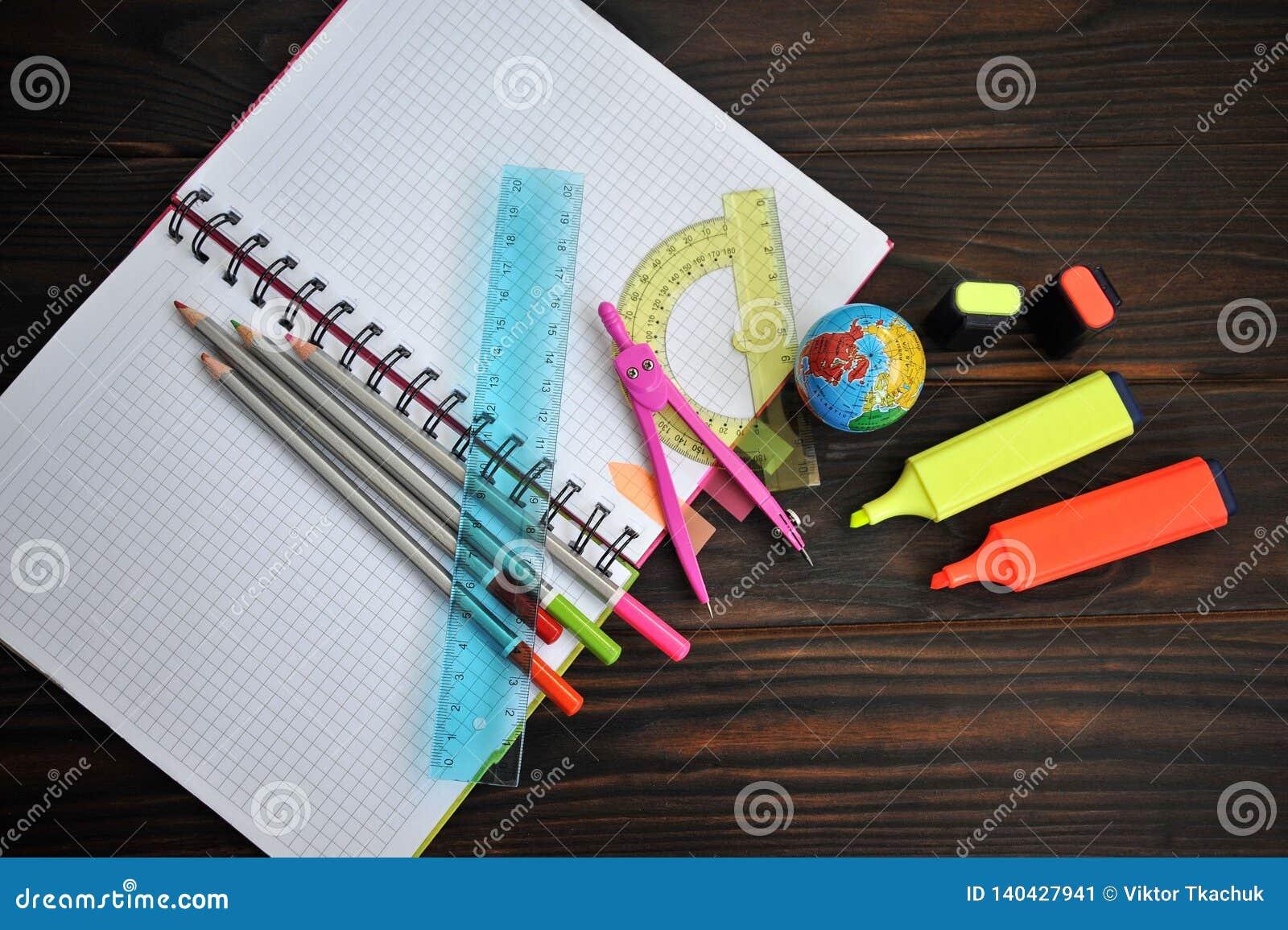 Materiały rozpraszał na notatnika lying on the beach na ciemnym drewnianym stole,