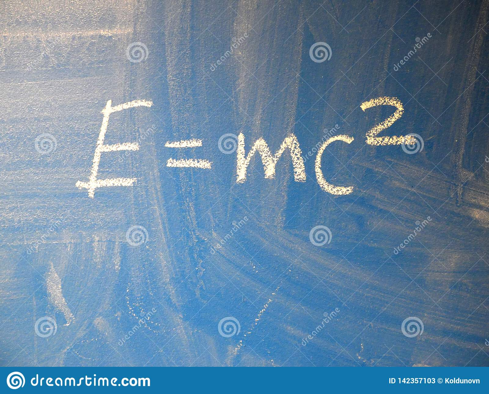 Mathematical formula e=mc2 squared written on a blue, relatively dirty chalkboard by chalk