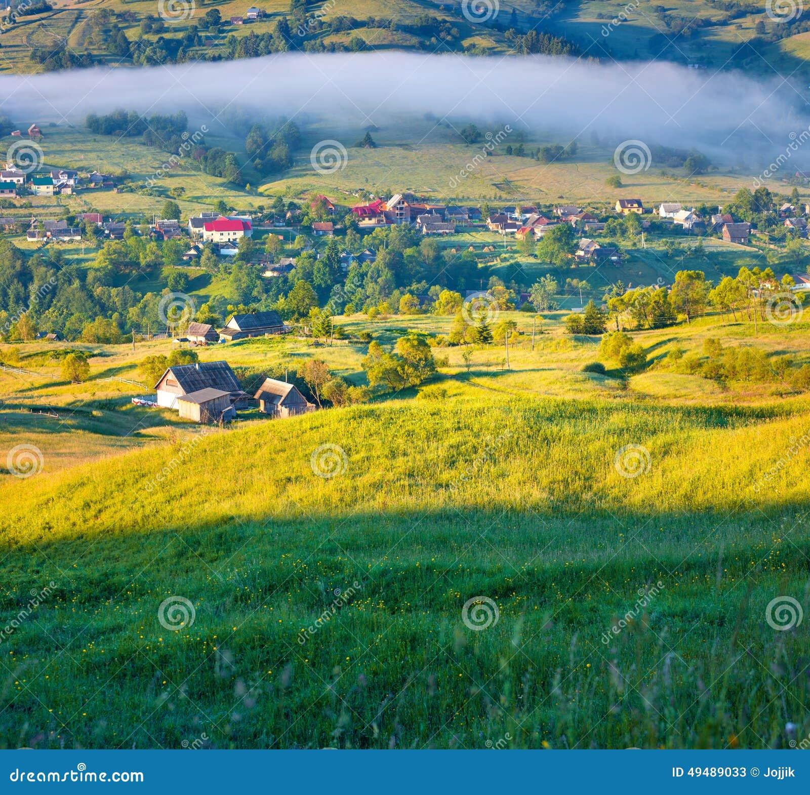 Matin brumeux d été dans le village de montagne