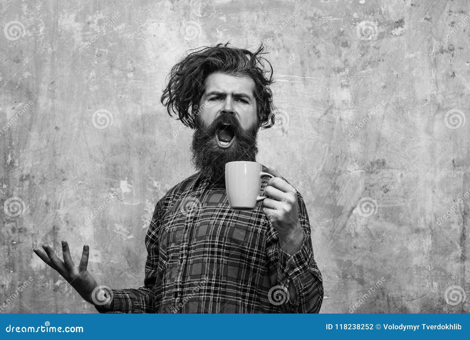 Matin Coffe homme barbu chanteur tirant les cheveux élégants de frange avec la tasse bleue