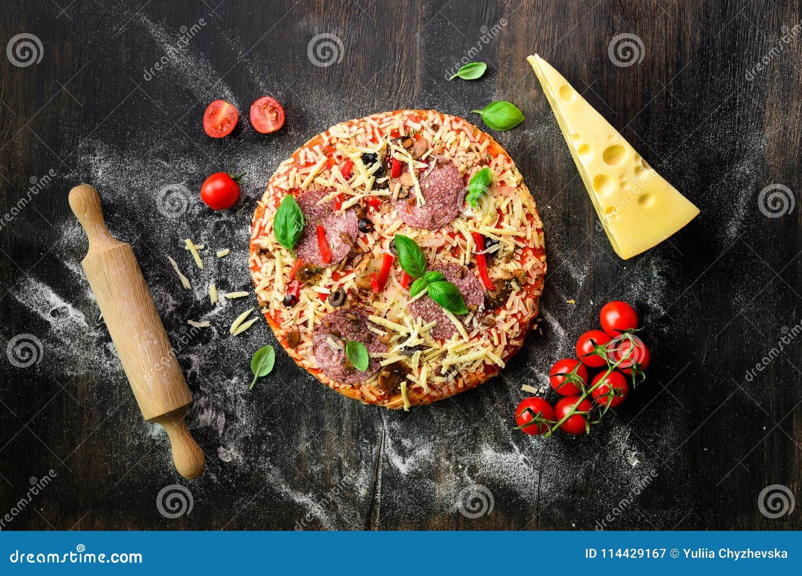 Matingredienser för italiensk pizza, körsbärsröda tomater, mjöl, ost, basilika, kavel, kryddor på mörk bakgrund överkant