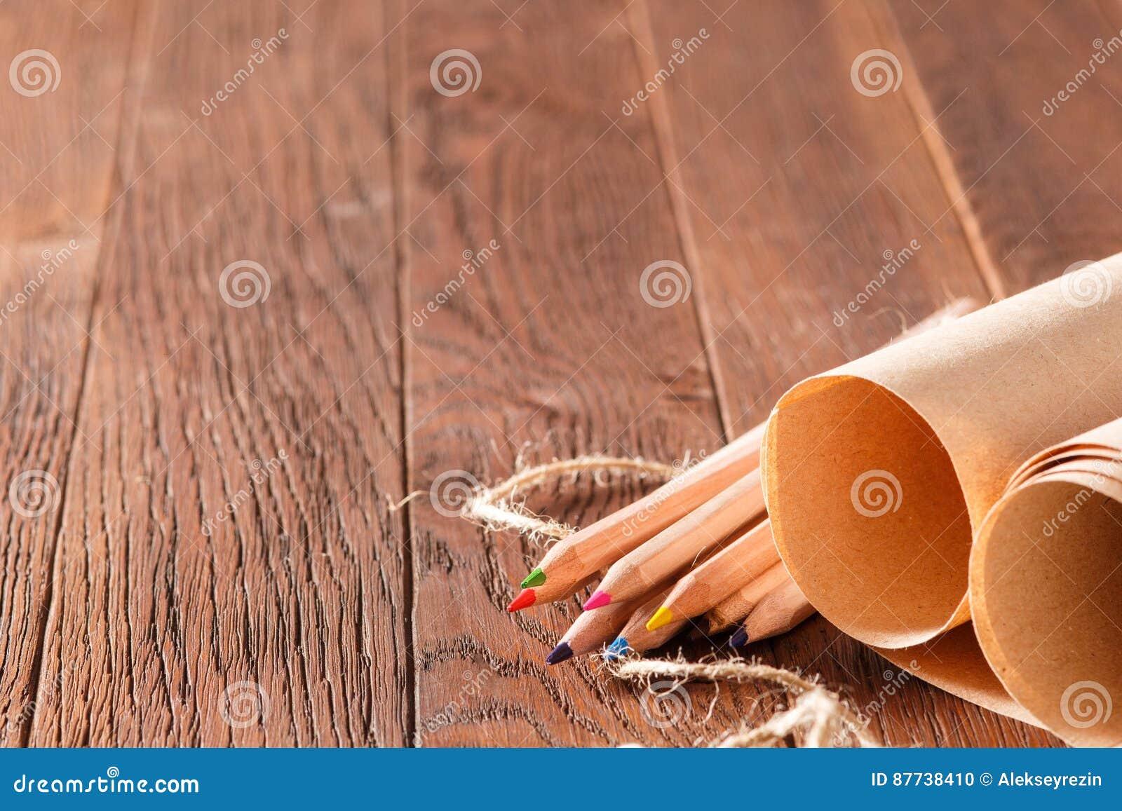 Matite in bianco di colore e della carta marrone sulla tavola di legno con la corda decorativa