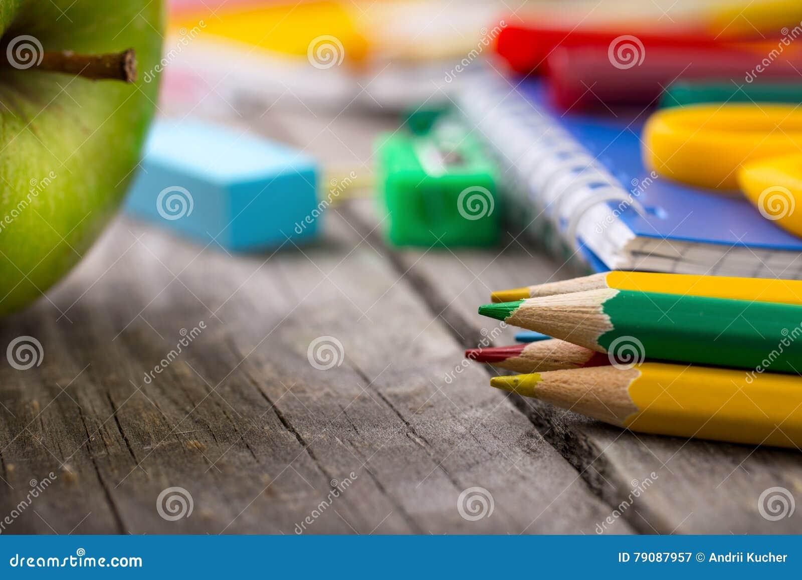 Matite colorate con i rifornimenti di scuola e la mela verde