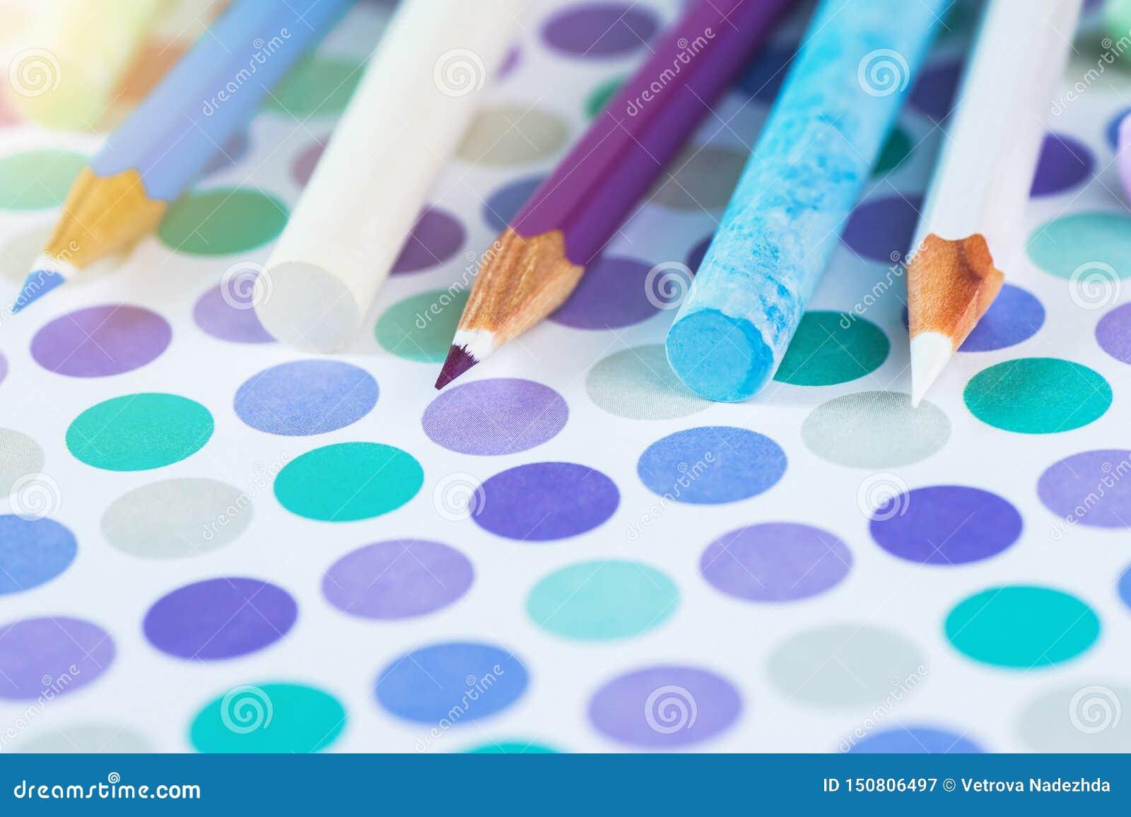 Matite e gesso colorati della scuola su un fondo pastello ad un punto con spazio per testo