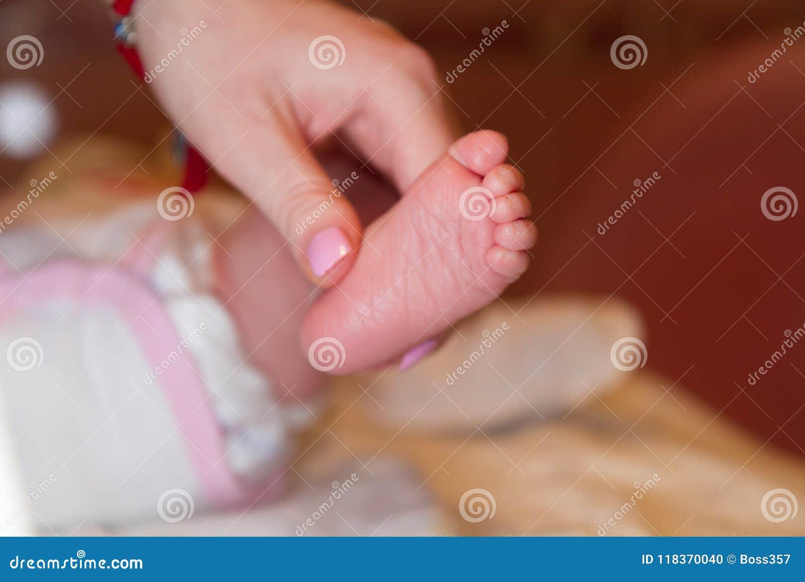 Matka chwytów ręka noga niemowlak, palce i mali cieki zdrowego dziecka,