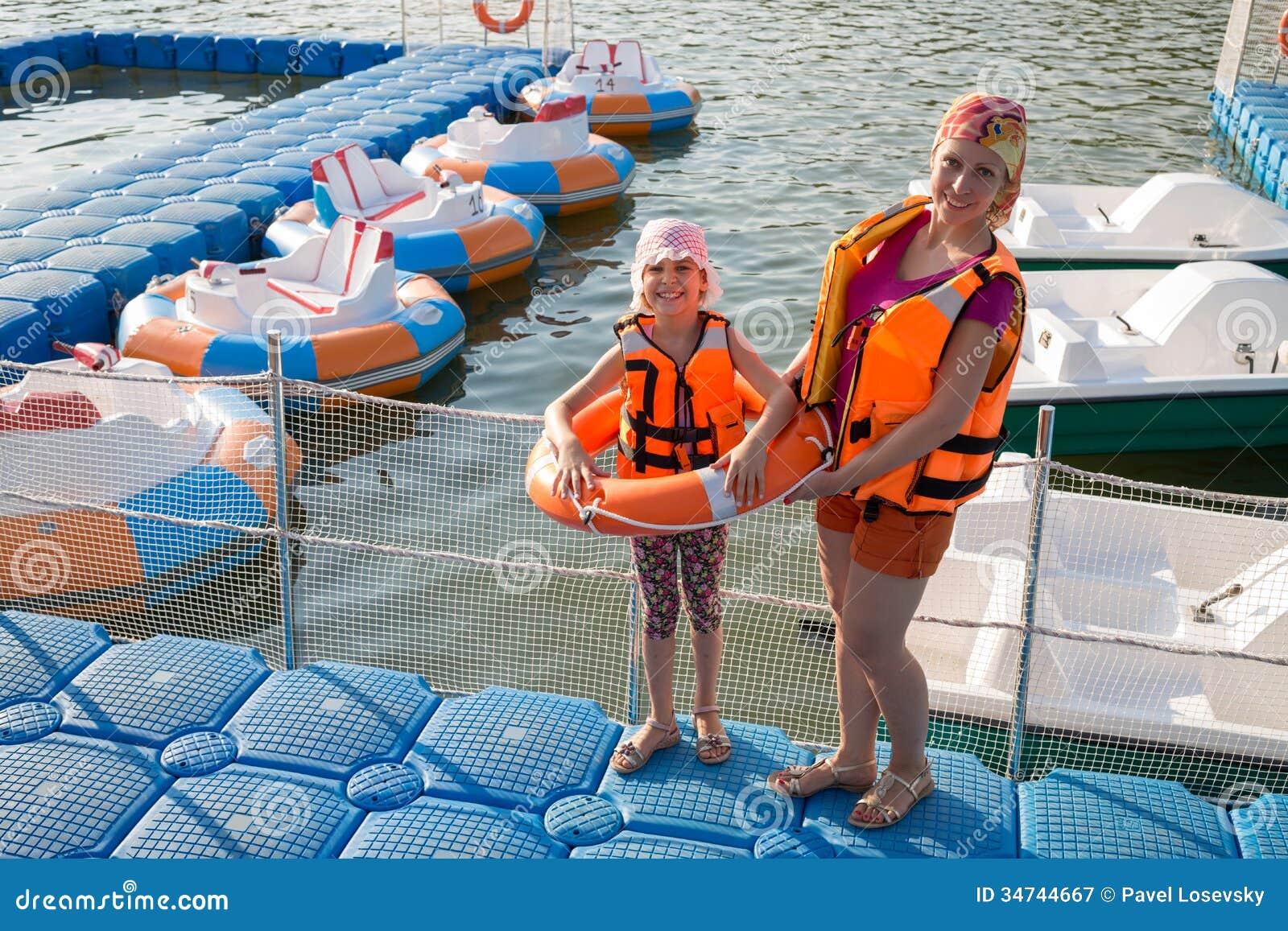 Matka i córka na doku z nadmuchiwanymi łodziami