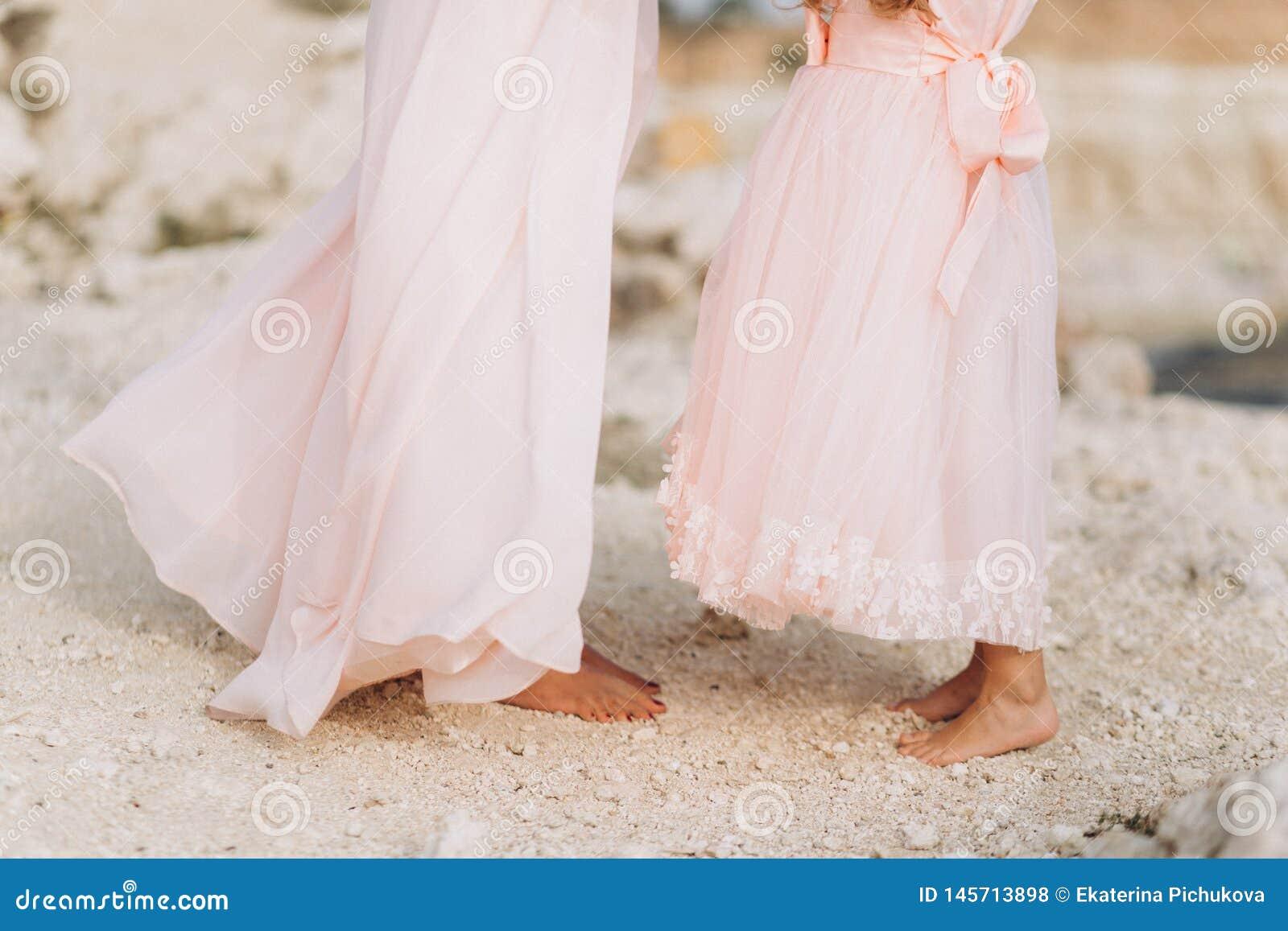 Matka i córka stoimy na skale w różowych sukniach