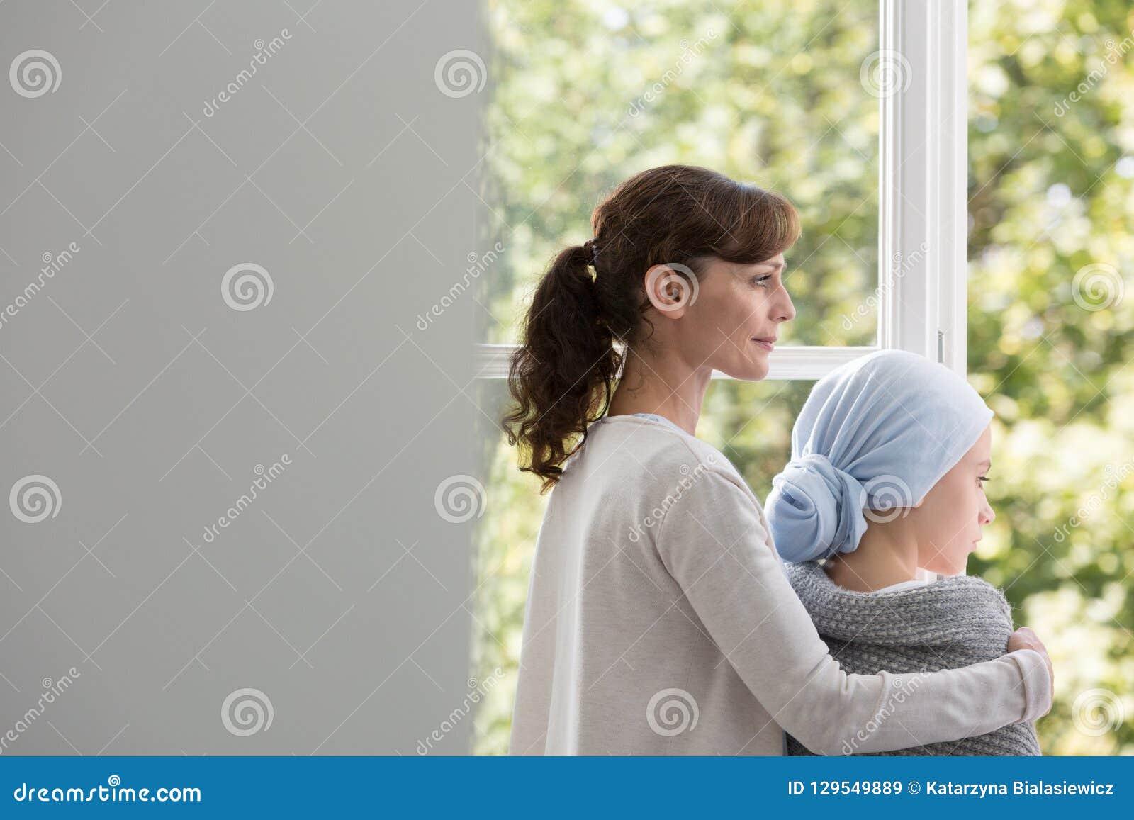 Matka i córka z nowotworem w szpitalu, patrzeje przez okno w centrum medycznym
